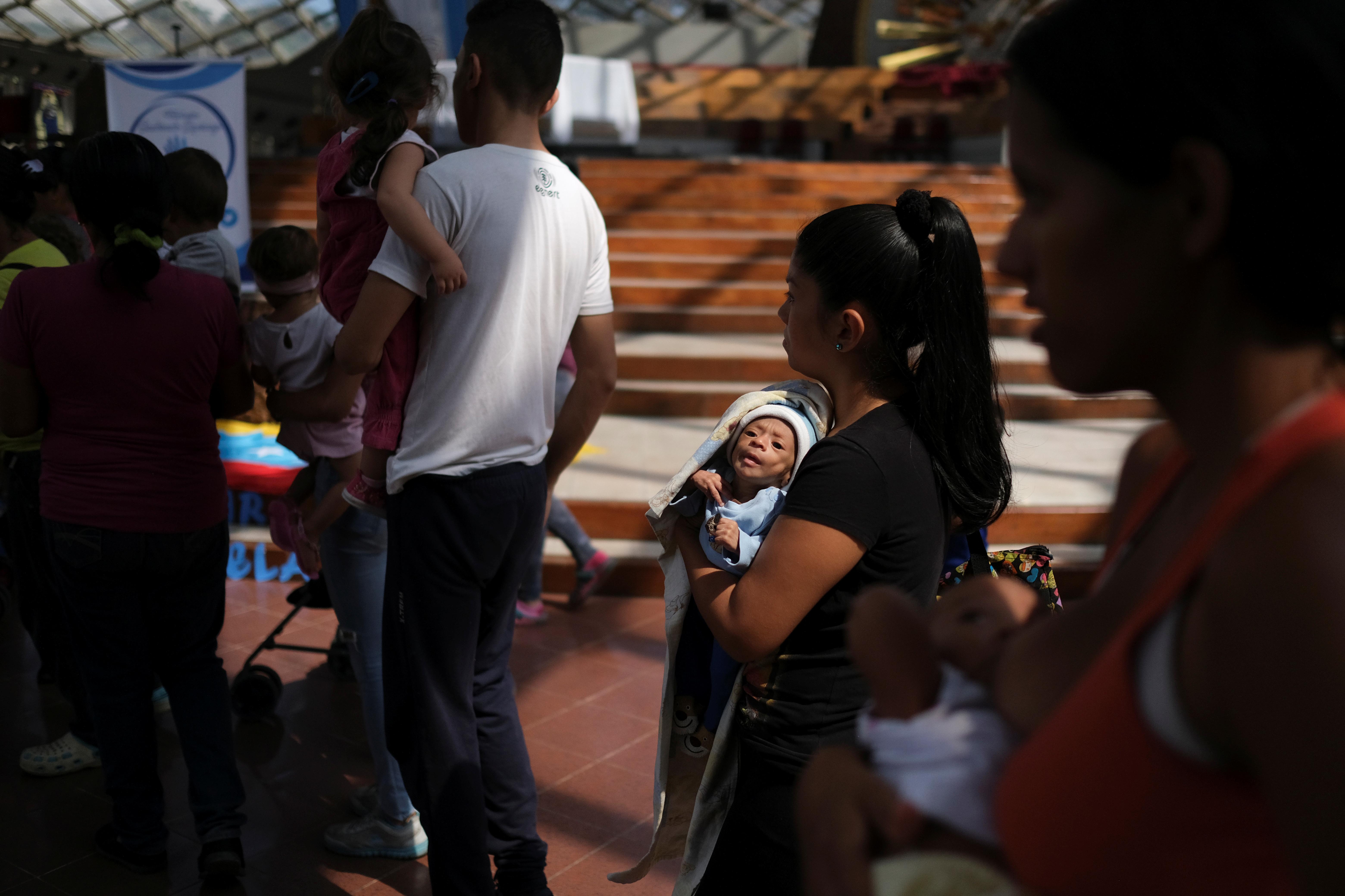Francys Rivero lleva a su hijo Kenai, que tiene dos meses y ha sido diagnosticado con desnutrición, mientras esperan ser vistos en un evento especial para niños con problemas nutricionales, organizado por la agencia católica de ayuda Caritas, en una iglesia en Barquisimeto (REUTERS/Carlos García Rawlins)