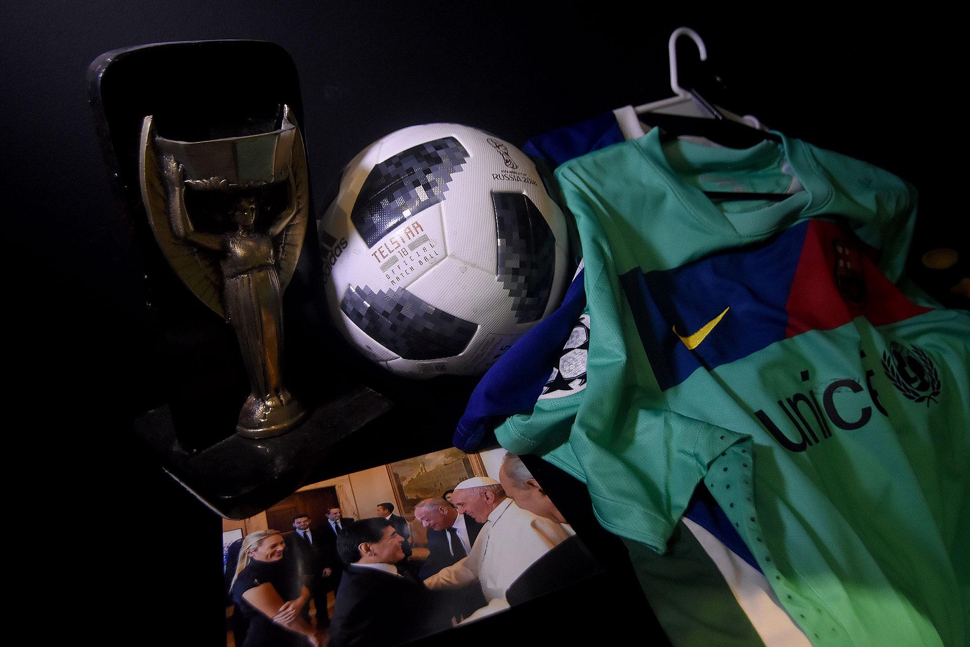 Variado: réplica de la vieja Copa del Mundo (trofeo Jules Rimet), balón Telstar usado en Rusia 2018, foto de Maradona con el Papa Francisco y camiseta alternativa del Barcelona (Nicolas Stulberg)