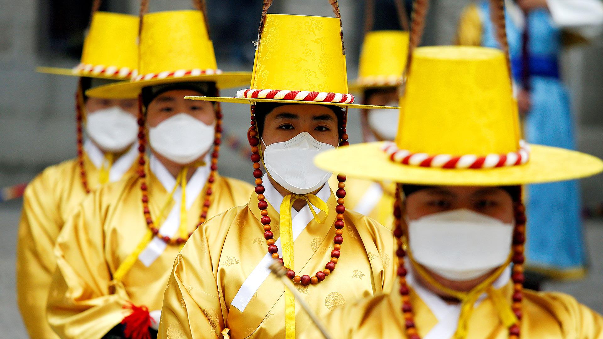 Trabajadores en trajes tradicionales coreanos usan máscaras protectoras para evitar contraer el coronavirus durante una recreación de la Ceremonia de Cambio de la Guardia Real frente al Palacio Deoksu en Seúl, Corea del Sur (REUTERS / Heo Ran)