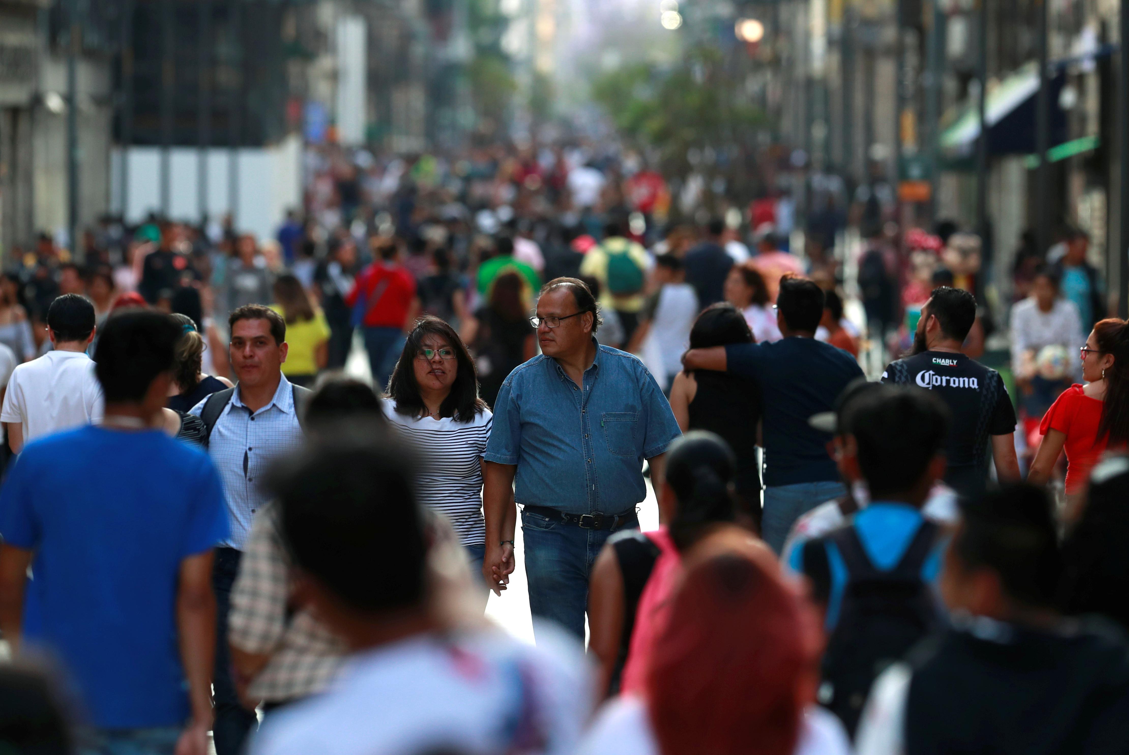 La gente camina en una calle peatonal cerca de la Plaza Zócalo cuando las autoridades de salud de México comenzaron a implementar medidas más estrictas para contener la propagación del coronavirus (COVID-19), en la Ciudad de México, México, 22 de marzo de 2020.