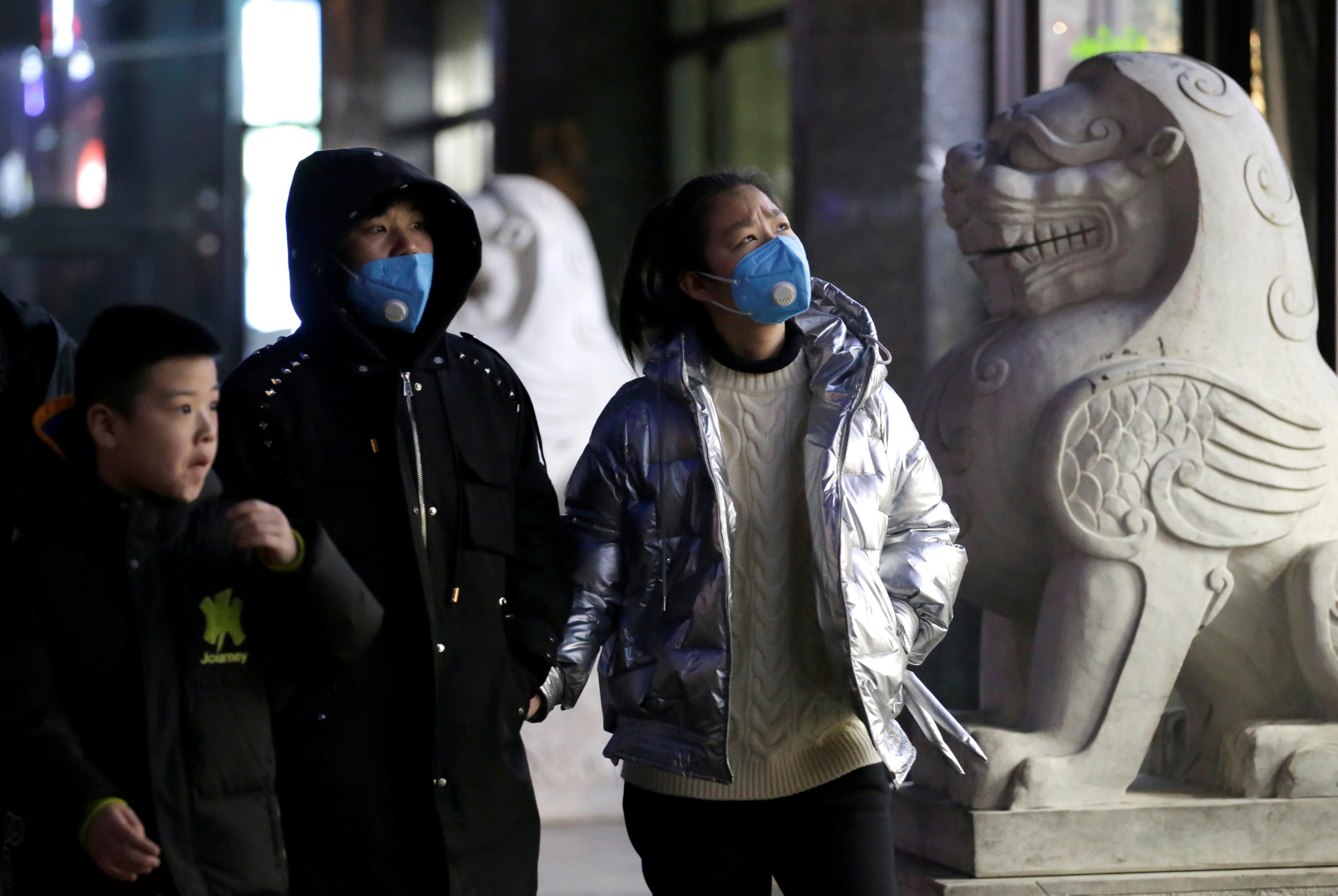 Personas con máscaras caminan por una calle en Beijing, China, 21 de enero de 2020. REUTERS / Jason Lee
