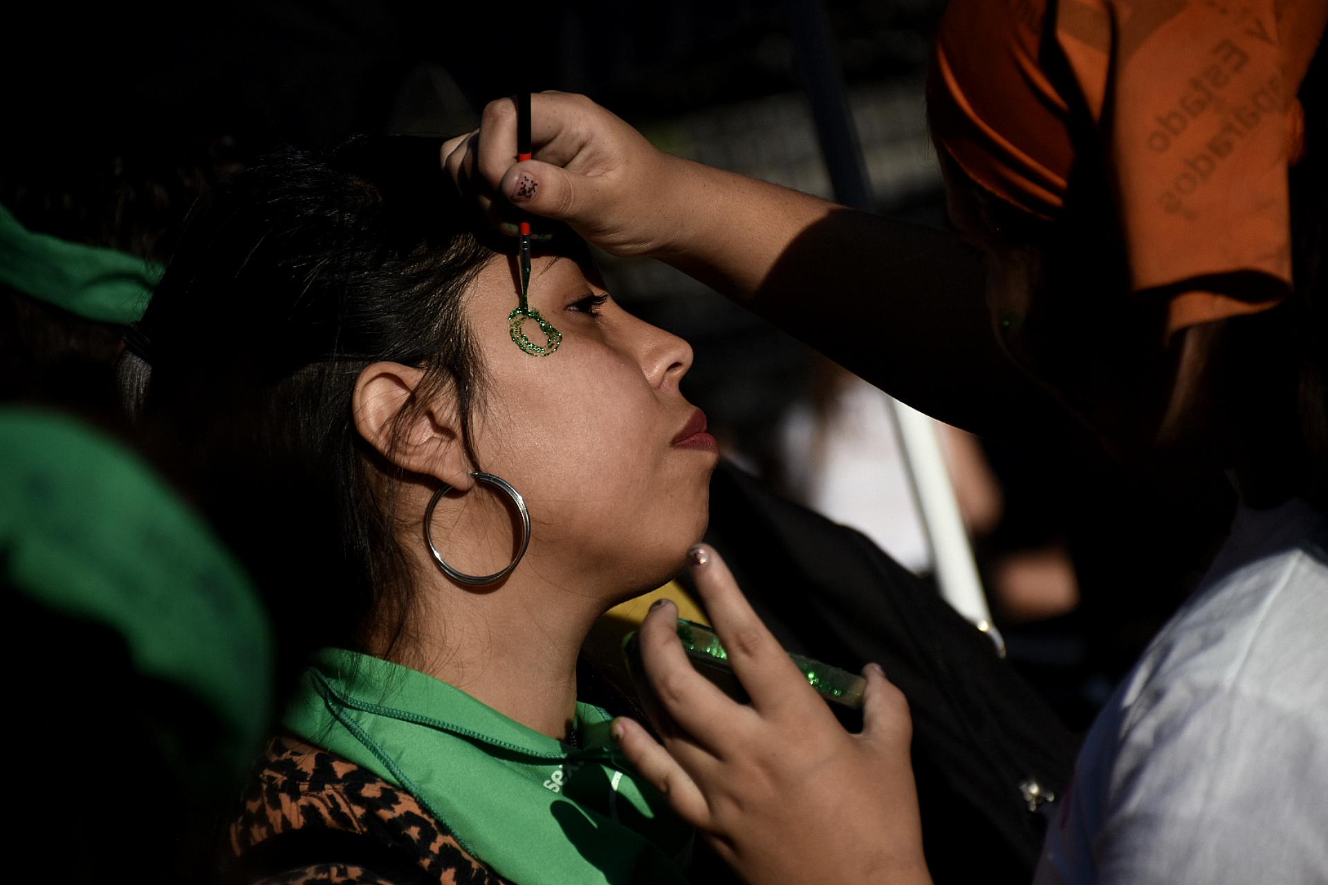 Una joven se pinta la cara con el color verde, símbolo del aborto legal