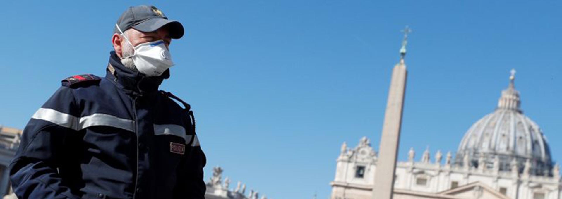 Un policía con mascarilla vigila una Plaza de San Pedro vacía desde Roma, Italia. (REUTERS/Guglielmo Mangiapane)