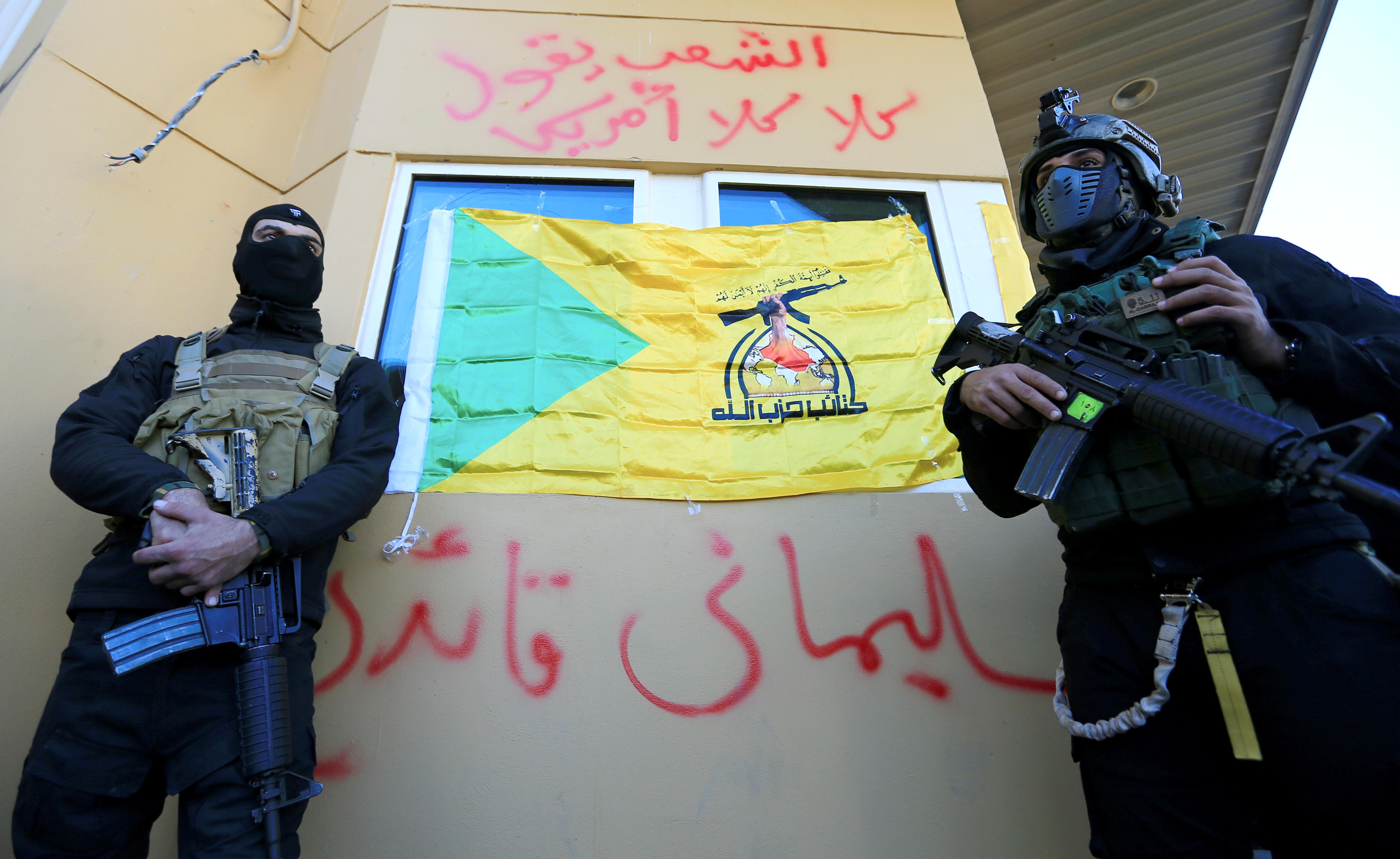 Una bandera de Hezbollah en Irak bloquea la visión de una de las ventanas de la embajada de EEUU en Bagdad