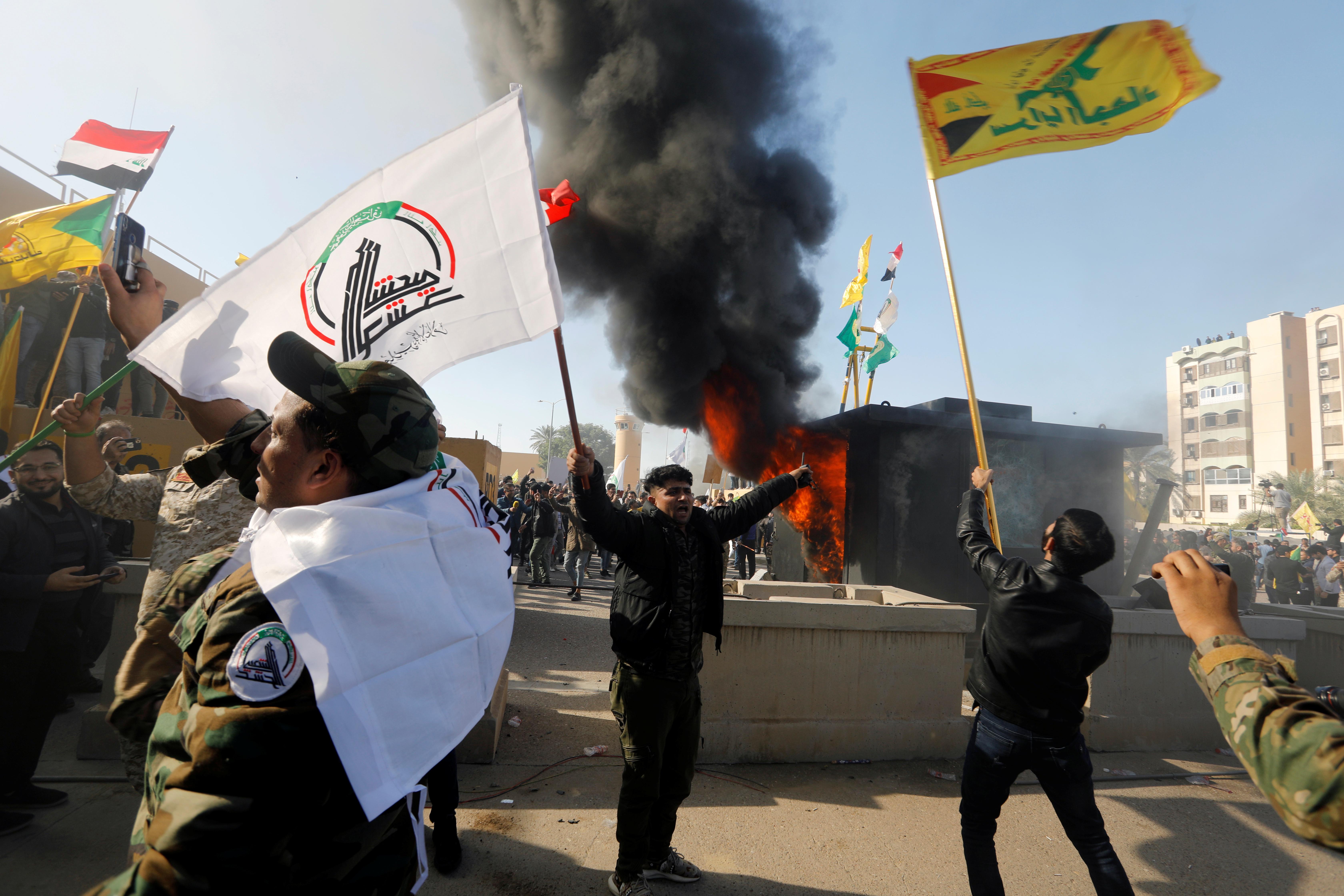 Los milicianos enarbolan banderas de Hezbollah y las milicias proiraníes frente a la embajada de EEUU