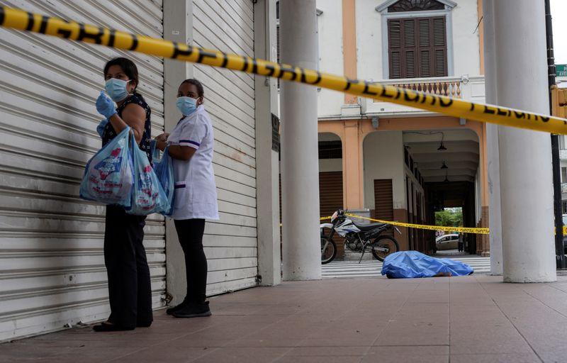 Dos mujeres con mascarillas pasan junto al cadáver de un hombre que se desplomó al suelo en Guayaquil, Ecuador (REUTERS/Vicente Gaibor)
