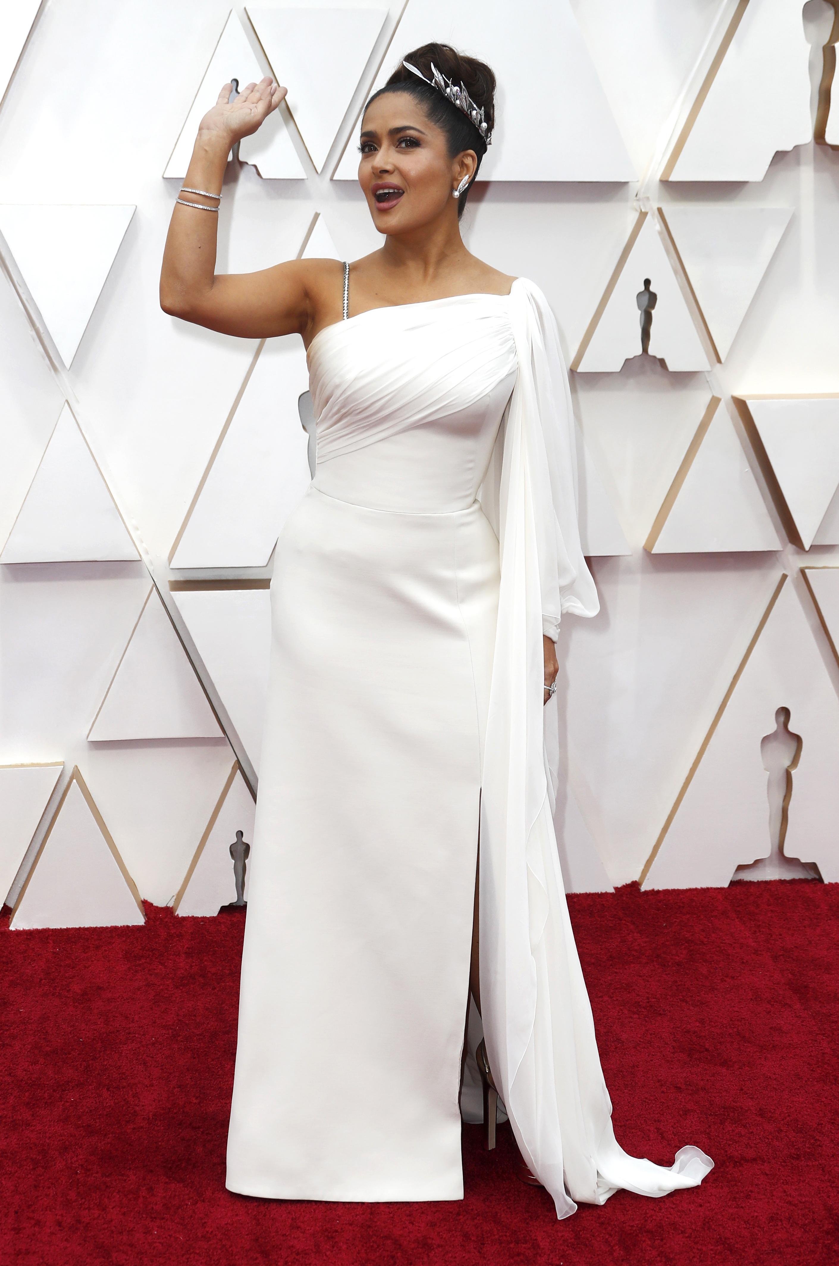 Apostando a un diseño total white con detalles de bretel finito de cristales, la actriz Salma Hayek, eligió a Gucci para la entrega de los Oscars. Un modelo de un solo hombro y con detalles de drapeado en la parte superior de la pieza