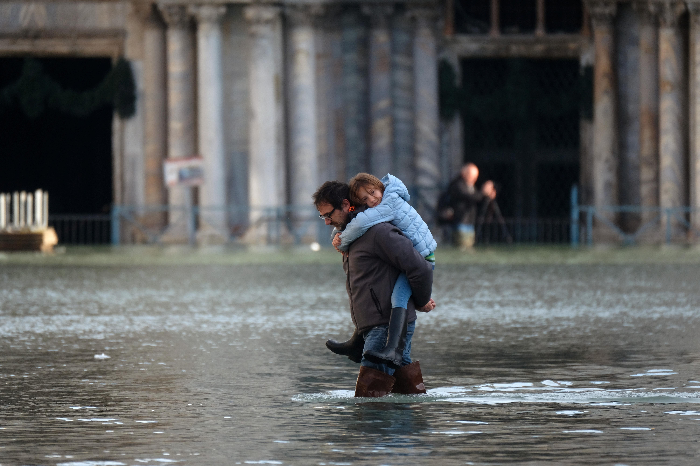Un hombre carga un niño mientras camina por la inundada Plaza de San Marcos durante la marea alta en Venecia (REUTERS/Manuel Silvestri)