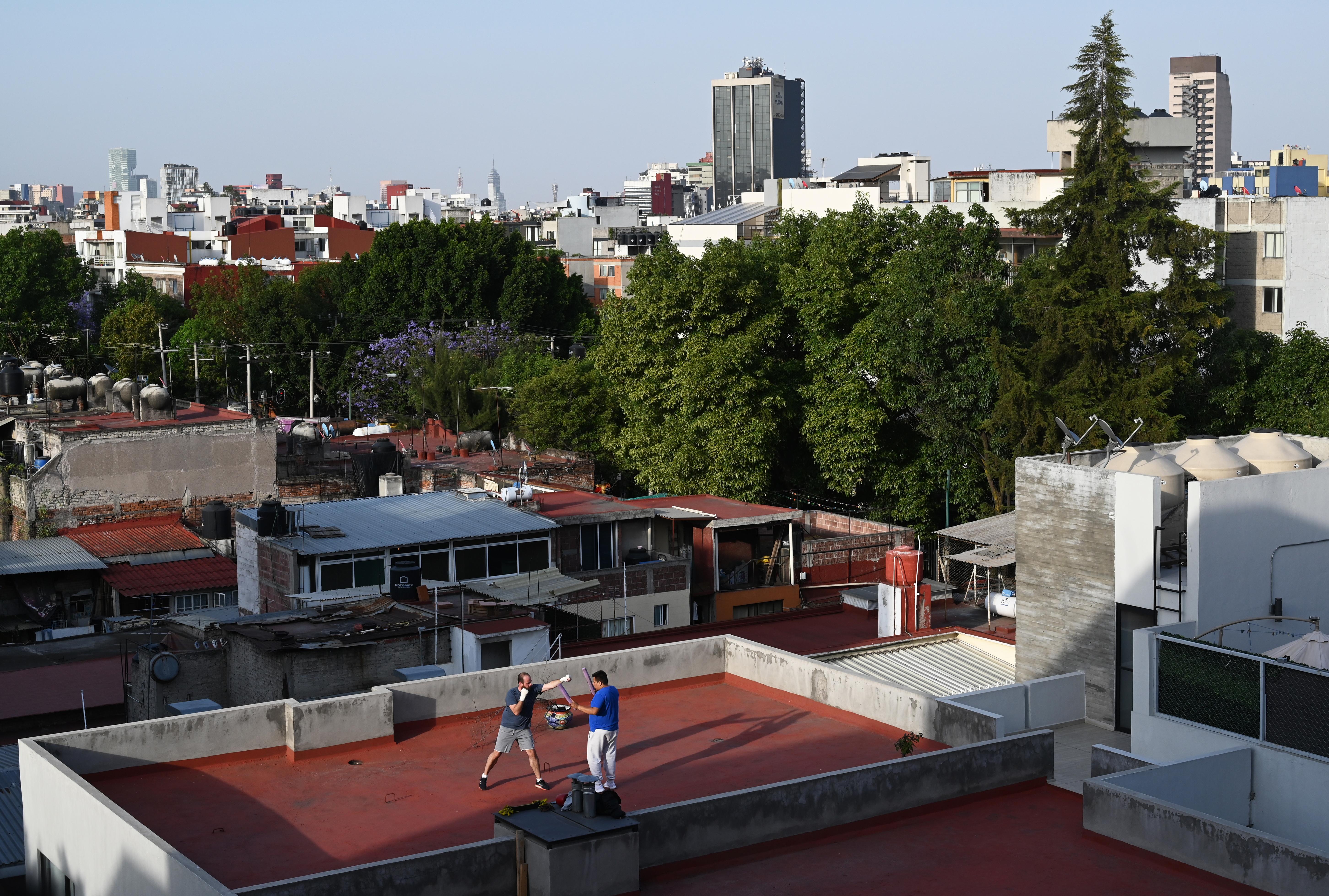 Un hombre practica boxeo con su entrenador en la azotea de un edificio en la Ciudad de México el 31 de marzo de 2020 durante la nueva pandemia de coronavirus COVID-19.