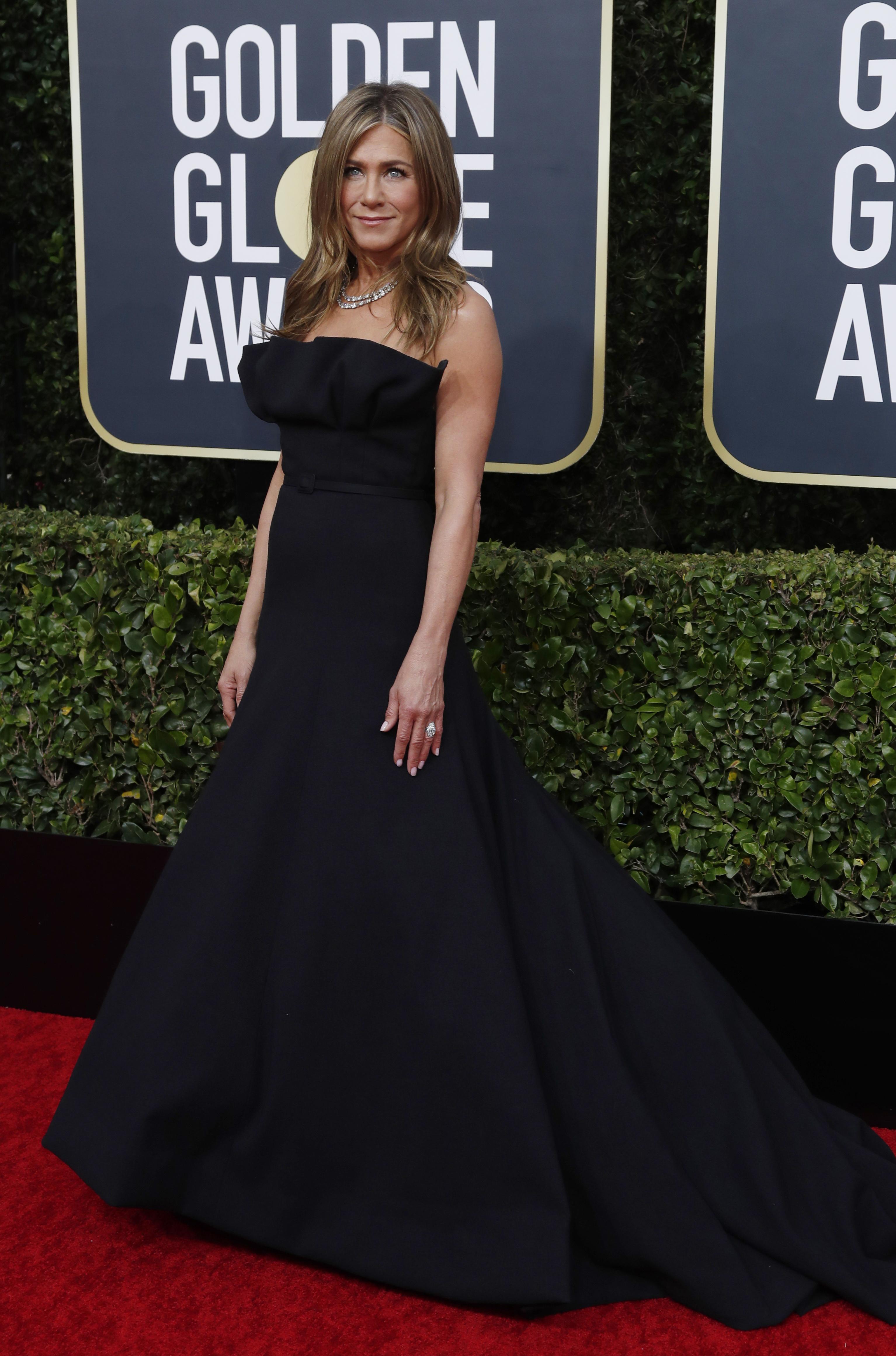 Jennifer Aniston deslumbró con su look total black con un strapless con cola y corte en la cintura. Completó su look con una gargantilla de brillantes y anillos