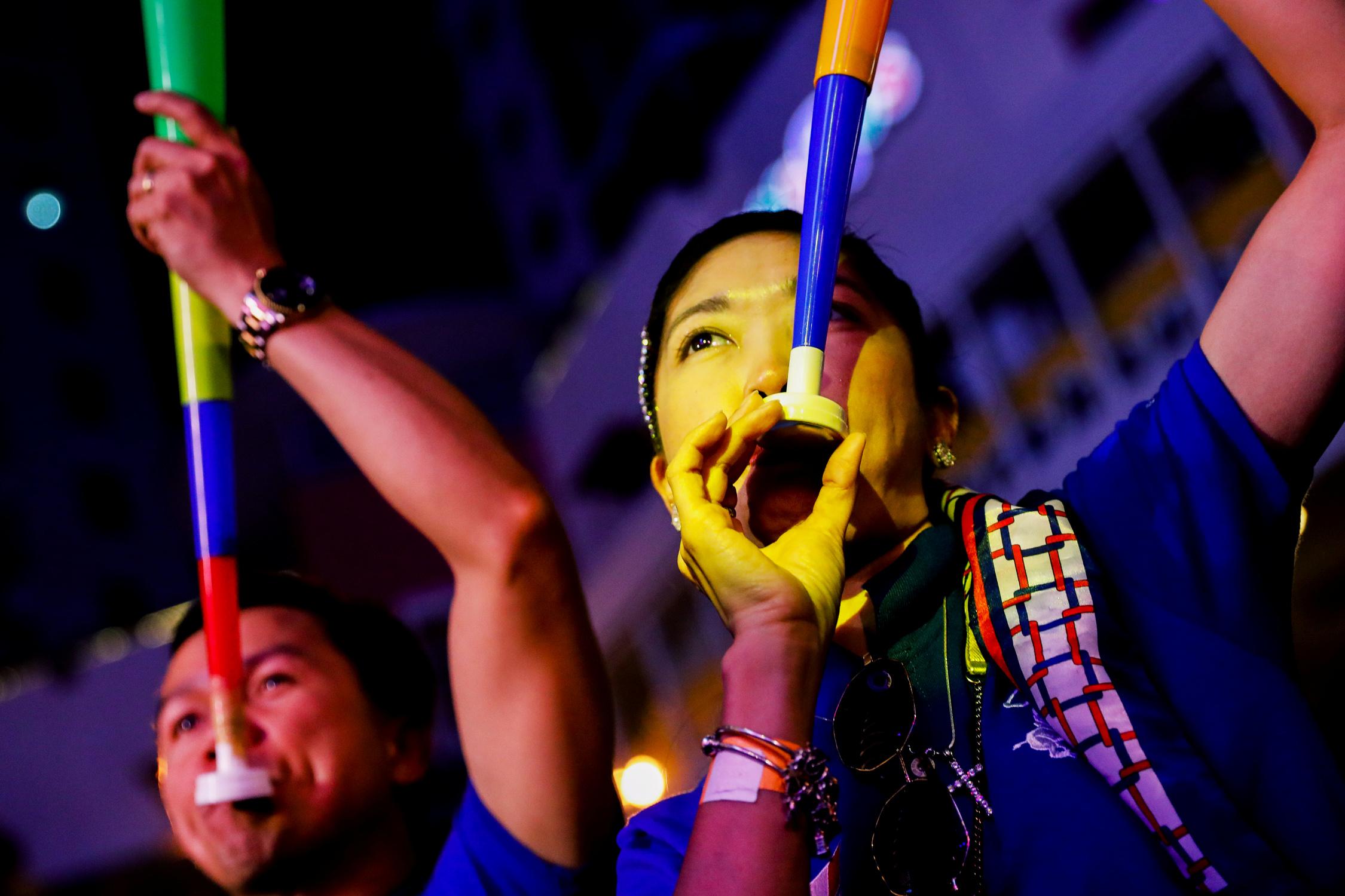 Festejos con trompetas de colores en las calles de Manila, Filipinas
