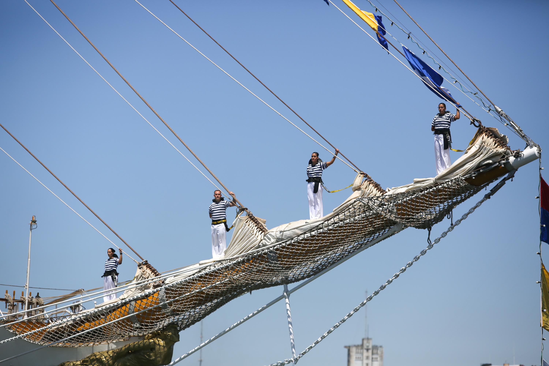 A medida de que la embarcación se acercaba comenzaron a escucharse los compases de la banda de abordo y a distinguirse en los tres mástiles a los marineros parados, como si se tratara de equilibristas