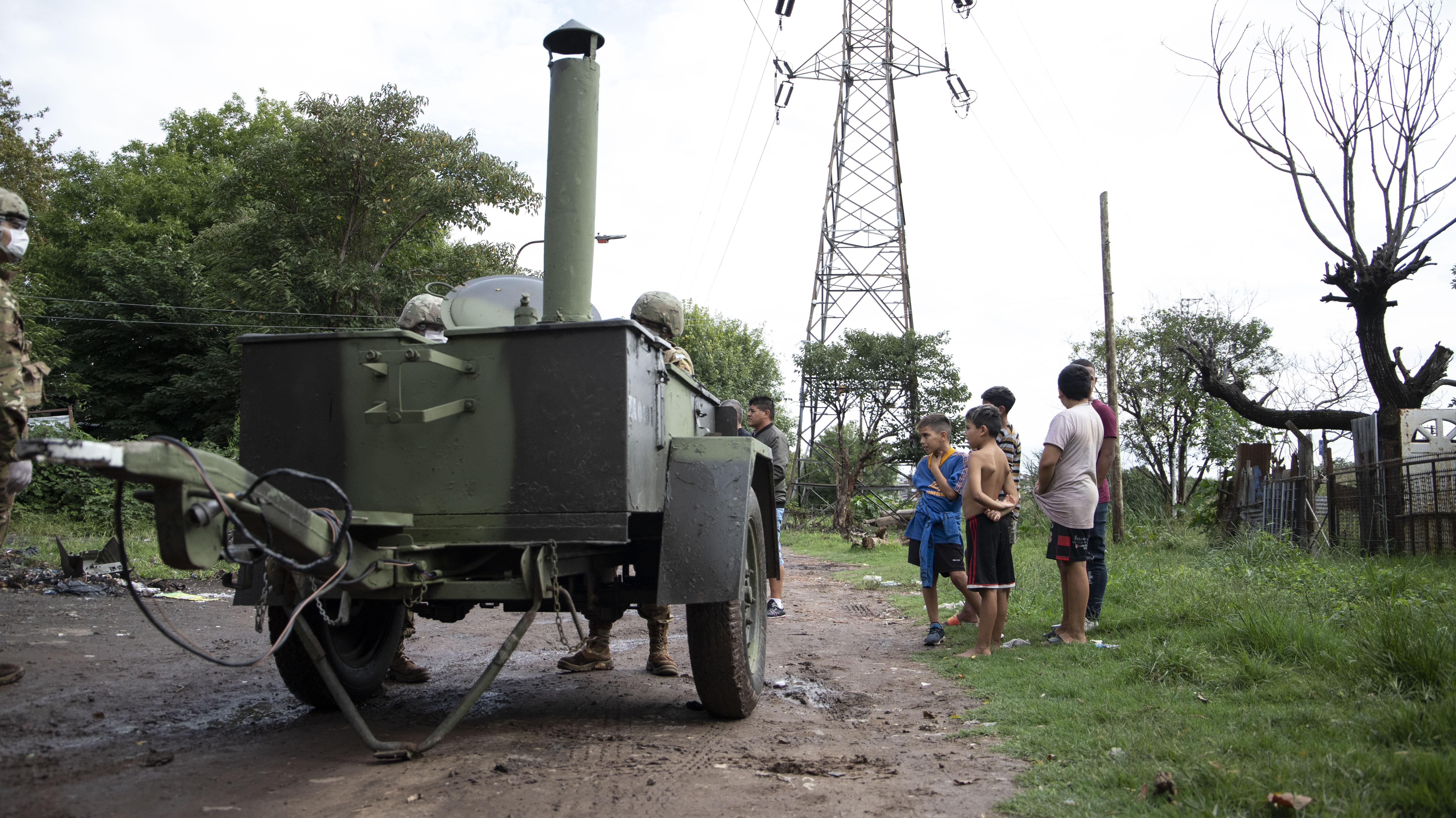 Un grupo de chicos espera un plato de comida en uno de los puntos de concentración del campamento militar