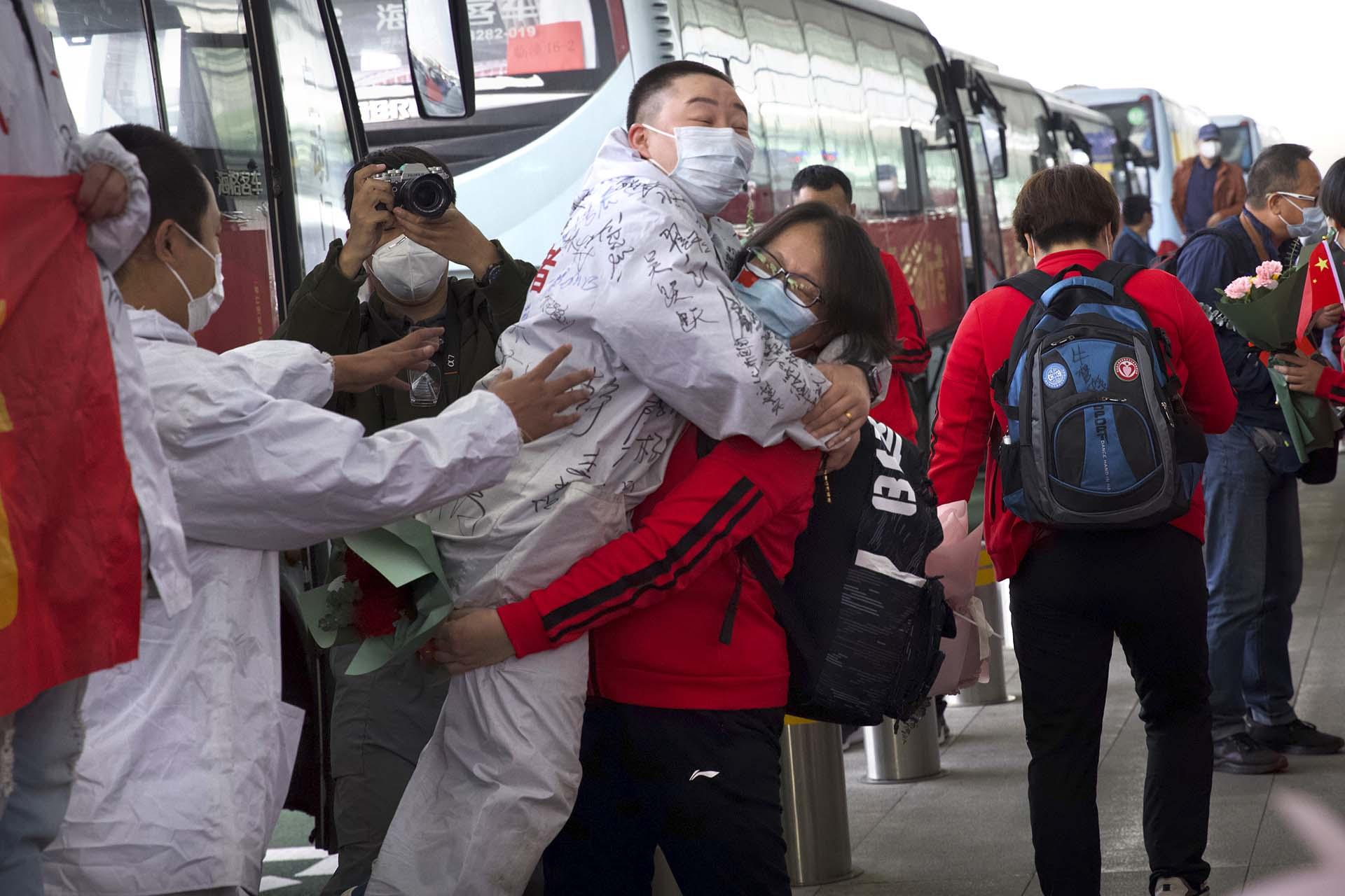 Un trabajador médico de la provincia china de Jilin abraza a un colega que se prepara para volver a su hogar en el Aeropuerto Internacional de Wuhan Tianhe (AP Photo/Ng Han Guan)