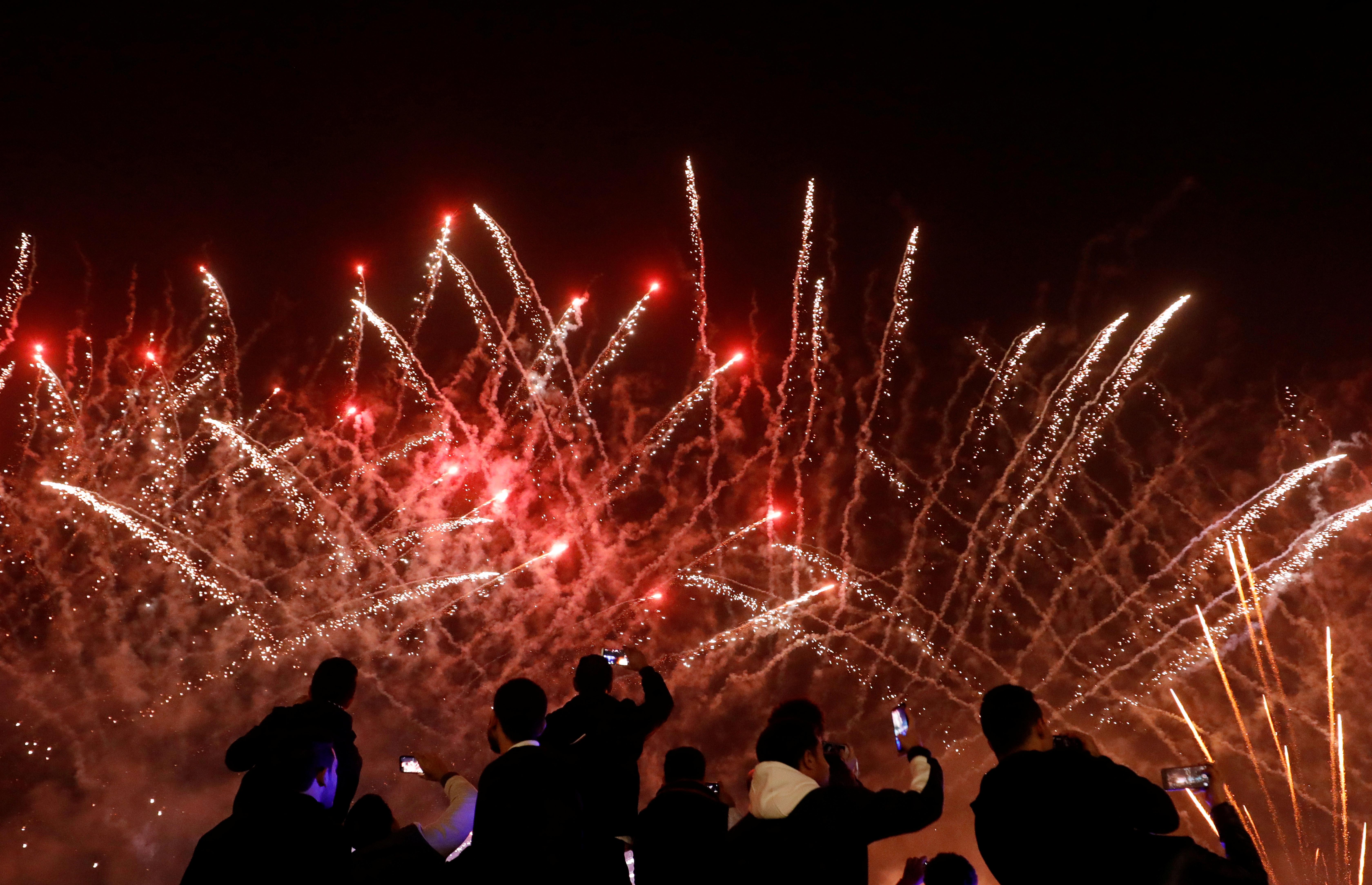 La gente graba fuegos artificiales en teléfonos móviles durante las celebraciones de Año Nuevo en el Canal de El Cairo, Egipto, el 1 de enero de 2020. (REUTERS / Amr Abdallah Dalsh)