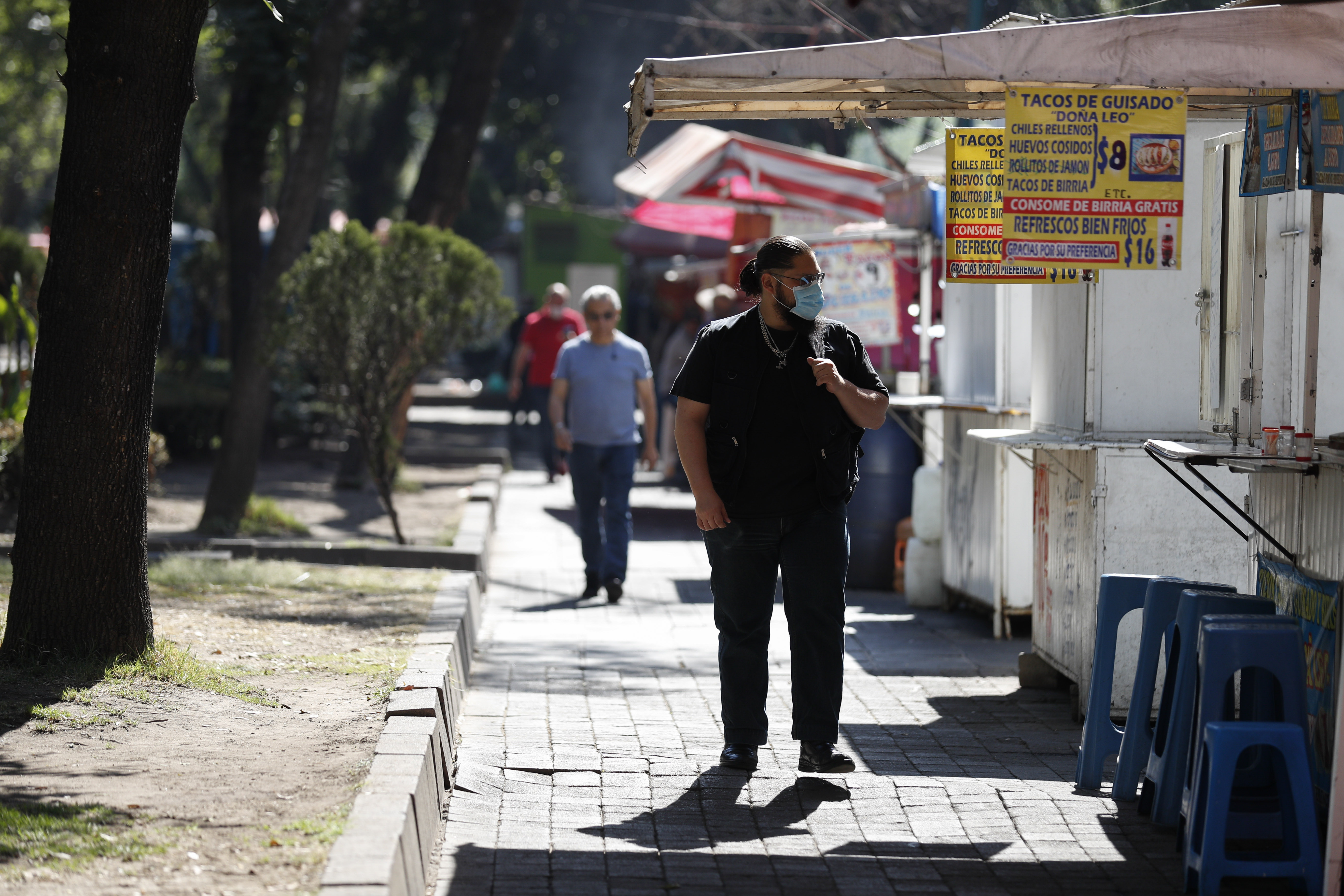 Un hombre con una máscara facial pasa por los puestos callejeros que venden alimentos, la mayoría de los cuales ya estaban abiertos , en la Ciudad de México, el miércoles 25 de marzo de 2020.