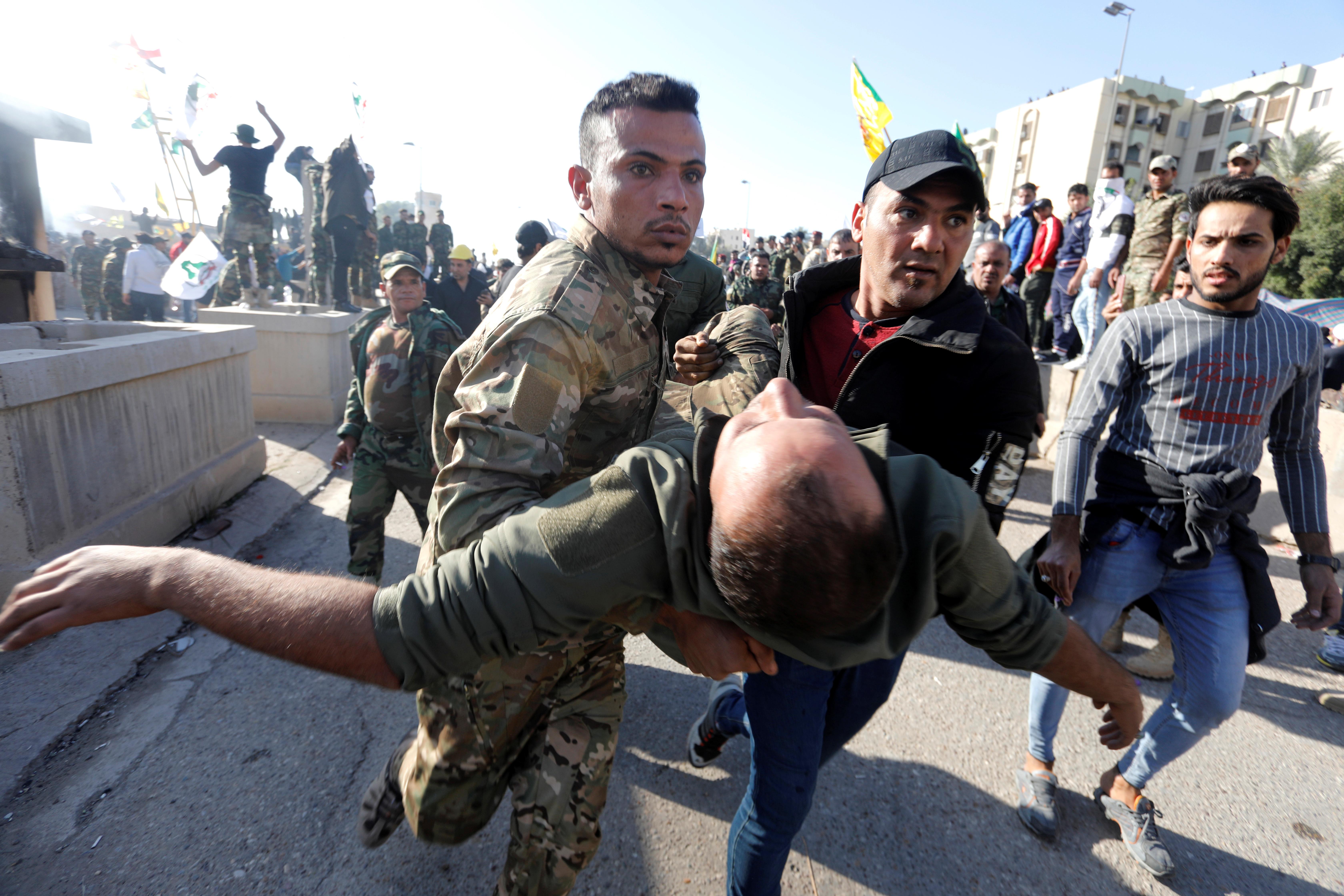 Un manifestante herido es trasladado por otros milicianos