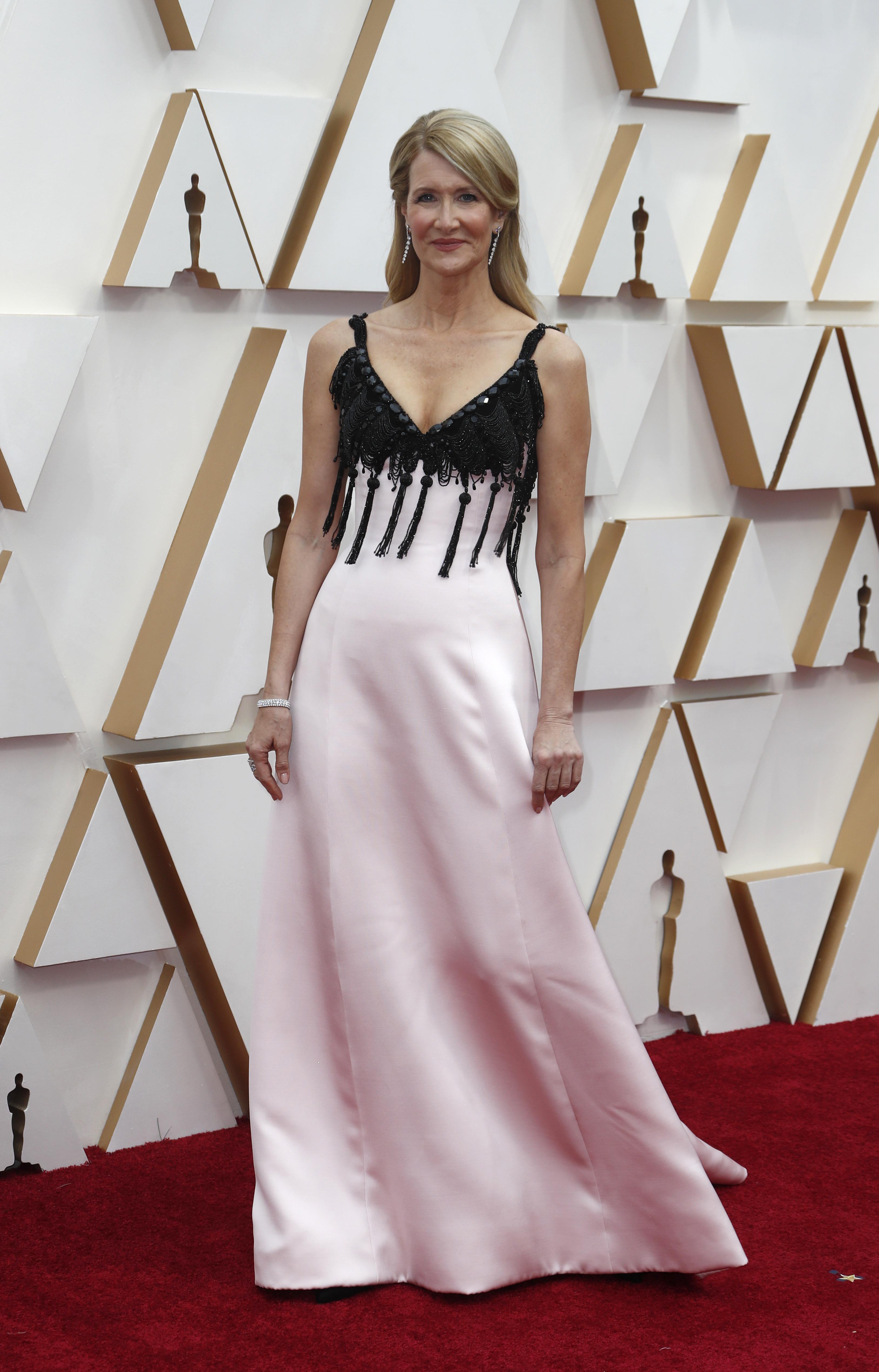 Laura Dern también apostó al rosa pero lo combinó con negro en la parte superior de la pieza con flecos y bordado. Completó su look con un brazalete de brillantes y aros gota. ¿Su beauty look? Un semi recogido y labios nude