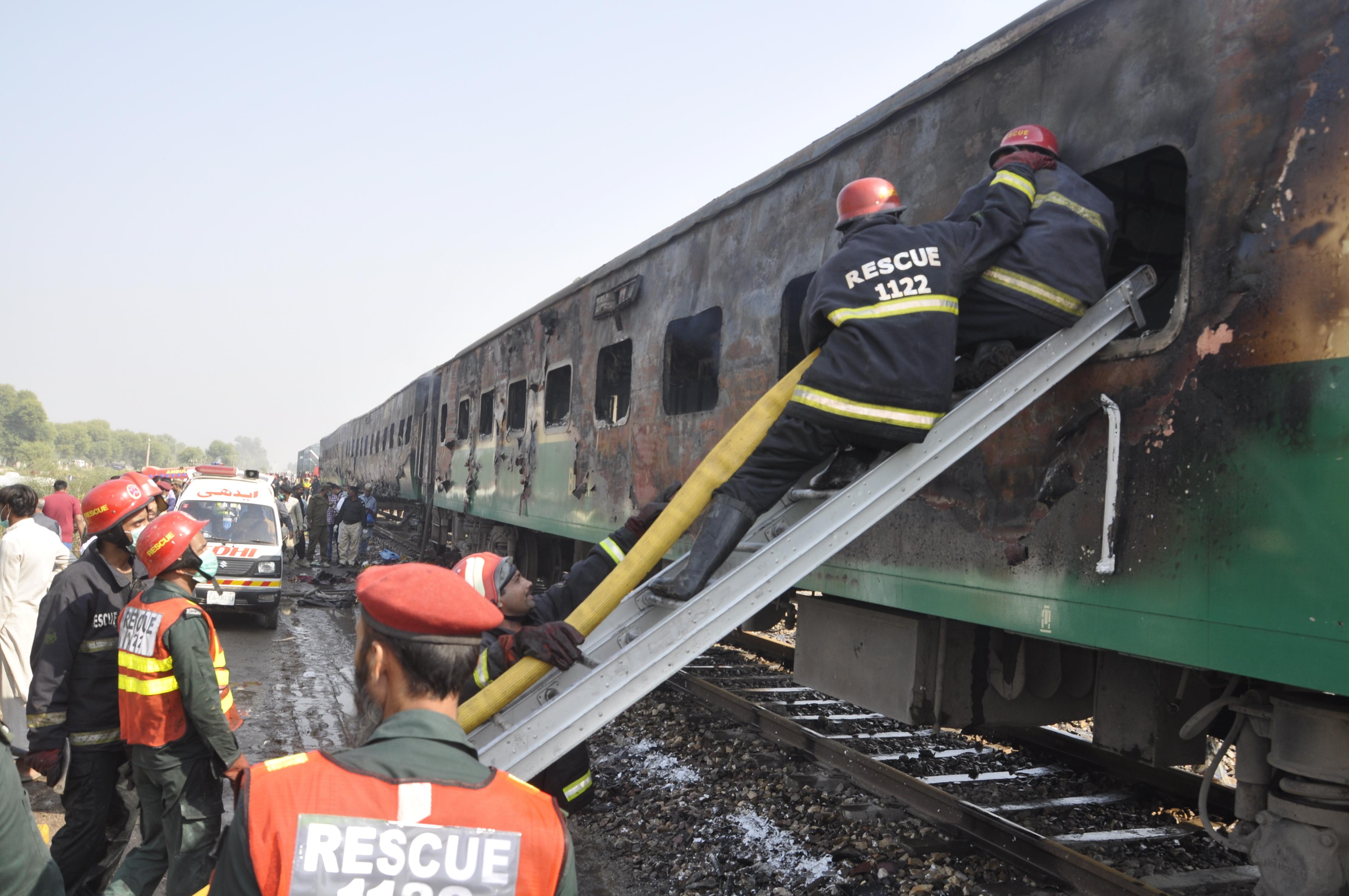 Los equipos de rescate buscan sobrevivientes después de un tren dañado por un incendio en Liaquatpur. (Foto AP / Siddique Baluch)