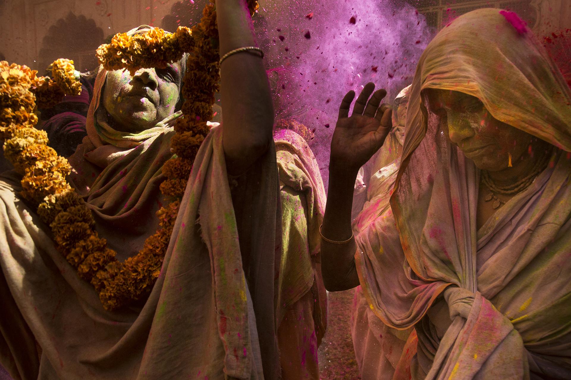 Un grupo de mujeres participa de la ceremonia Holi, el festival del amor y los colores que en una época era considerado inapropiado para las viudas, en el templo de Gopinath, en la India. Amy Toensing, 2016