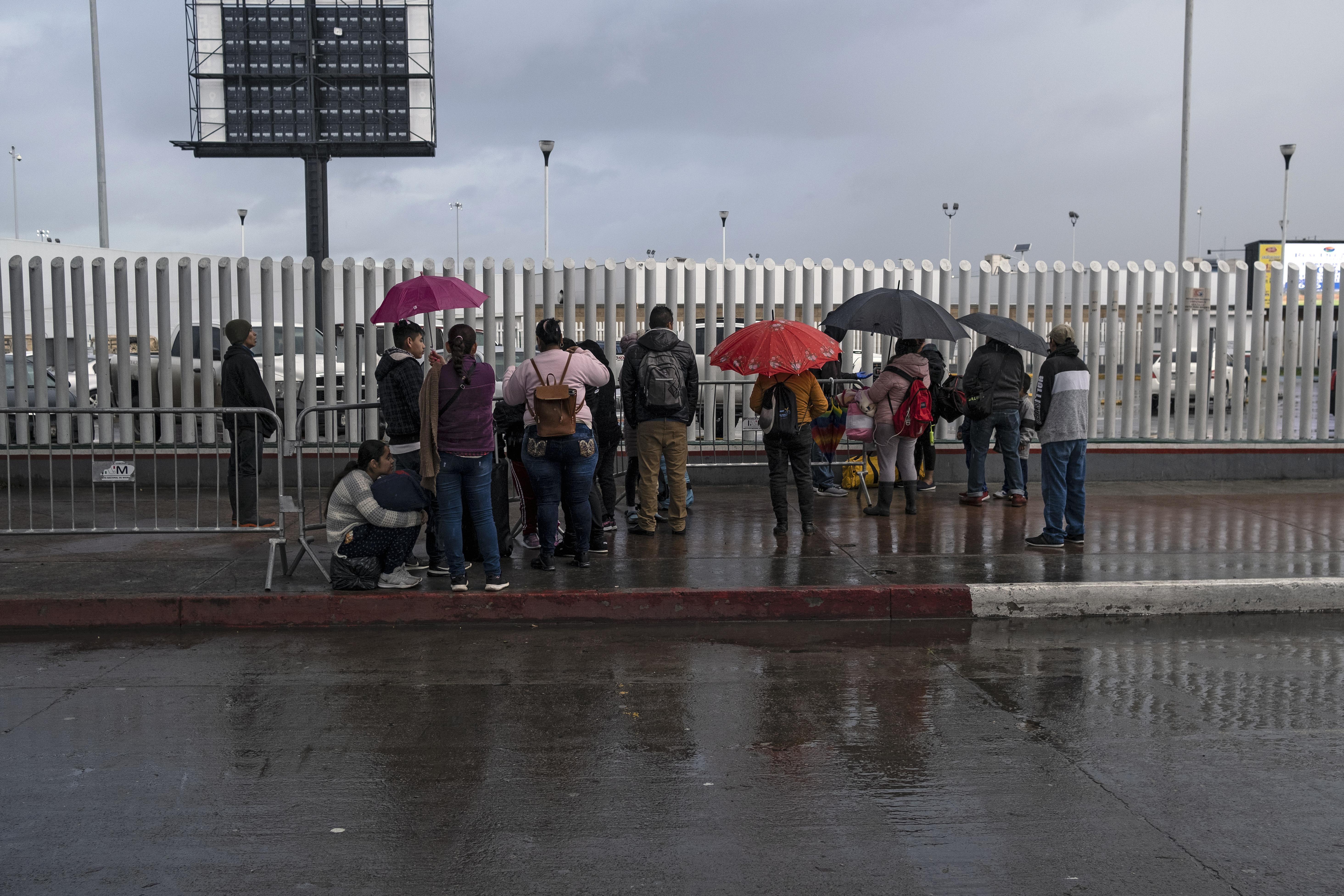 Los solicitantes de asilo esperan noticias fuera del puerto de entrada de El Chaparral en la frontera entre Estados Unidos y México en Tijuana, estado de Baja California, México, el 19 de marzo de 2020.