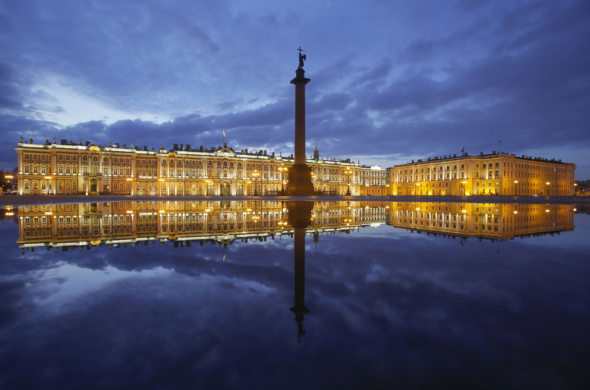 El Palacio de Invierno y la Columna de Alejandro se reflejan en un charco después de la lluvia en la Plaza del Palacio en San Petersburgo, Rusia, el lunes 27 de abril de 2020. (Foto AP / Dmitri Lovetsky)