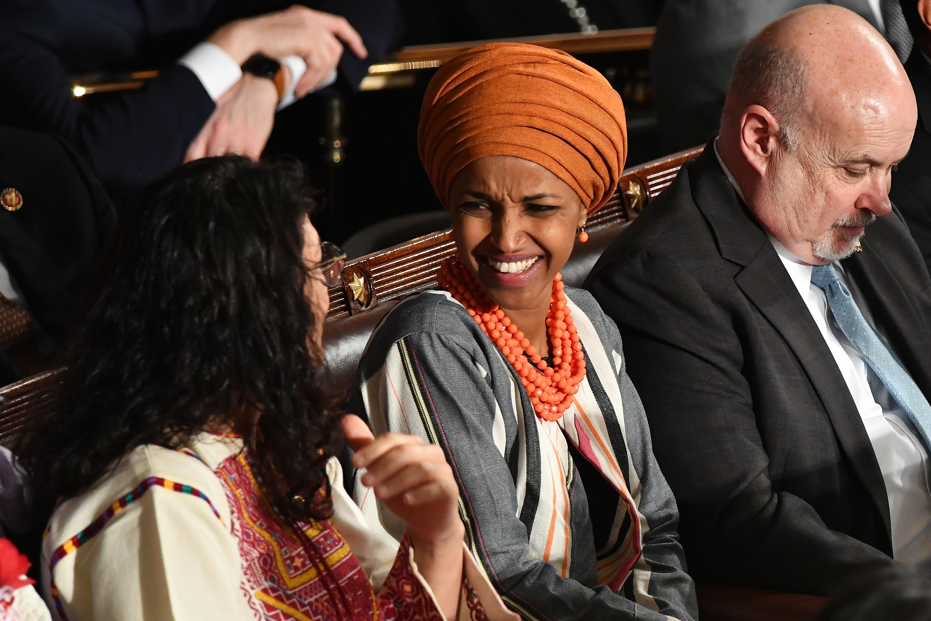 La congresista de Minnesota Ilhan Omar (derecha) y la congresista de Michigan Rashida Tlaib sonríen el presidente de los Estados Unidos, Donald Trump, pronuncia el discurso. (MANDEL NGAN / AFP)