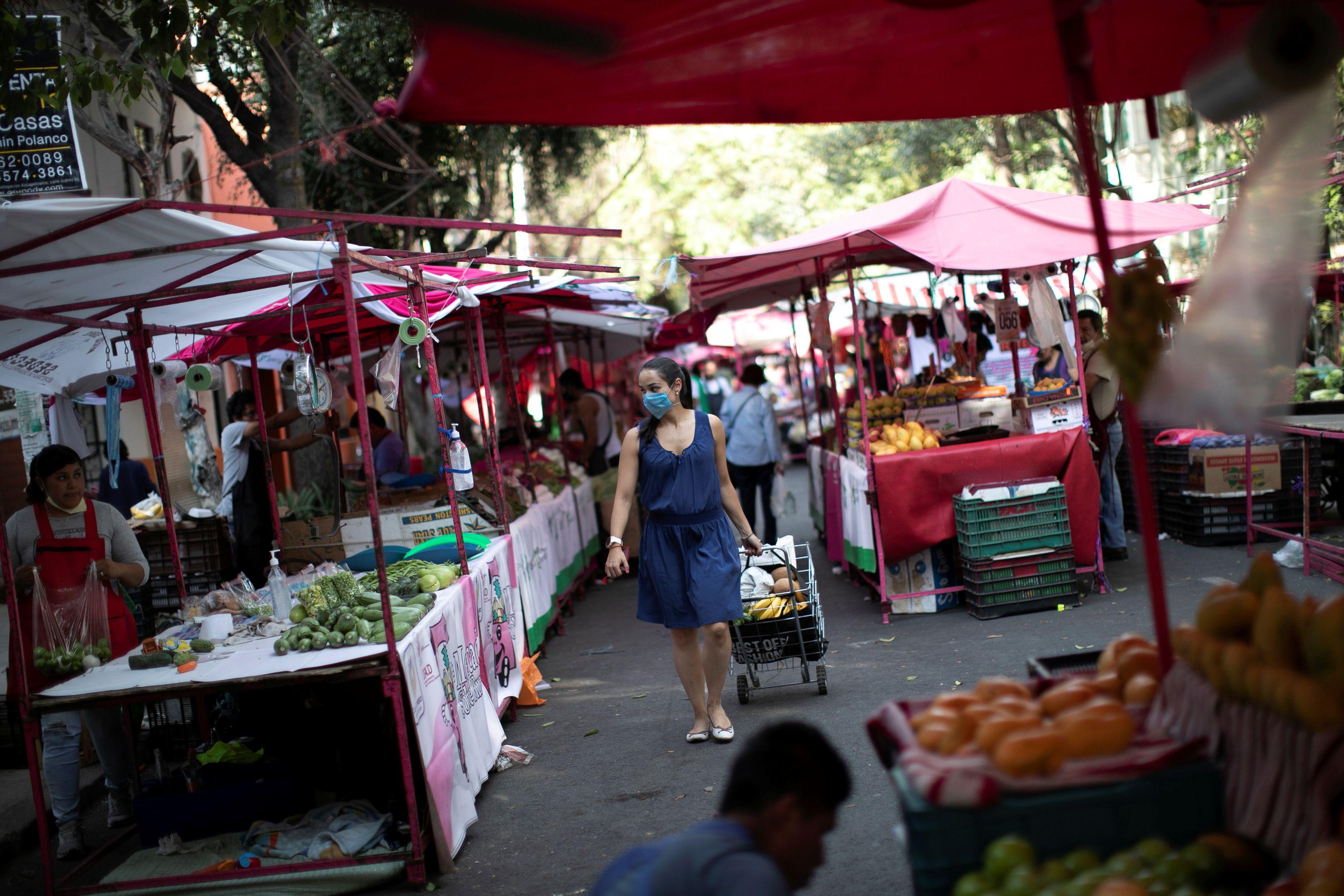 Se muestra a una mujer entre vendedores en el mercado callejero local después de que el gobierno de México declara una emergencia de salud el lunes y emite reglas más estrictas que contienen la enfermedad de coronavirus de rápida propagación (COVID-19), en la Ciudad de México, México, el 31 de marzo de 2020.