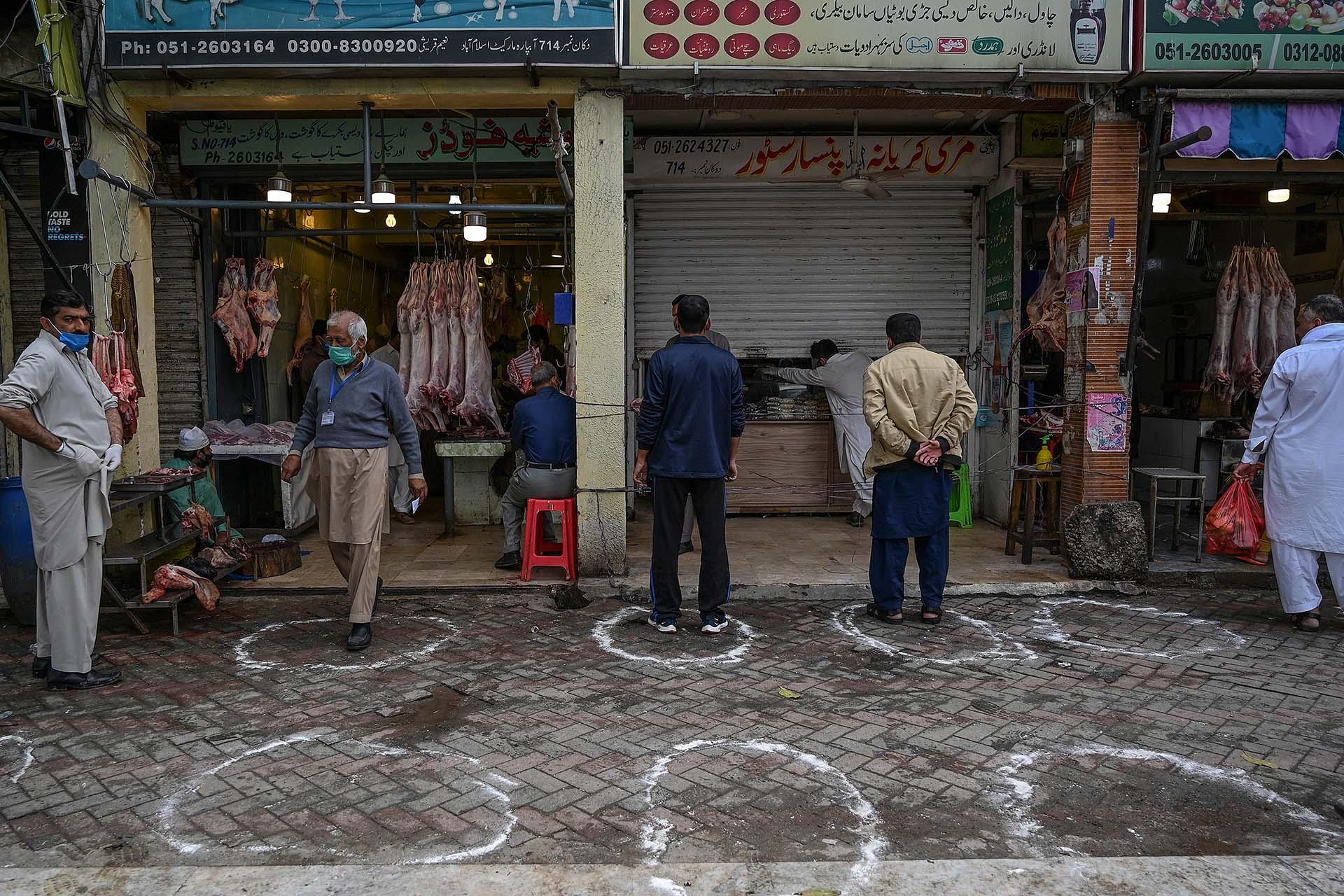 Clientes esperan su turno frente a una canicería en Islamabad, Pakistán.