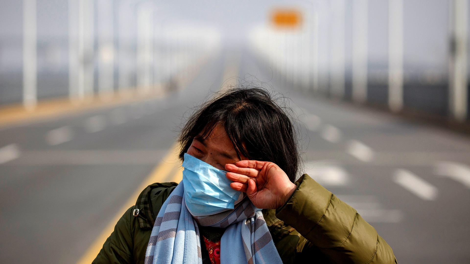 Una madre reacciona cuando le ruega a la policía que permita que su hija pase un punto de control para el tratamiento del cáncer después de llegar de la provincia de Hubei al puente del río Jiujiang Yangtze en Jiujiang, provincia de Jiangxi, China (REUTERS / Thomas Peter)