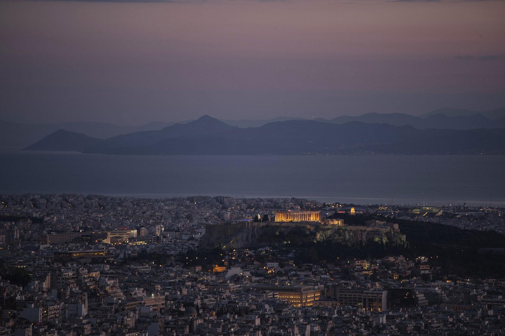 La Acrópolis de Atenas, Grecia, iluminada mientras la isla de Aegina se alza en el fondo y detrás de ella las distantes costas de la península del Peloponeso, el viernes 24 de abril (Foto AP / Petros Giannakouris)