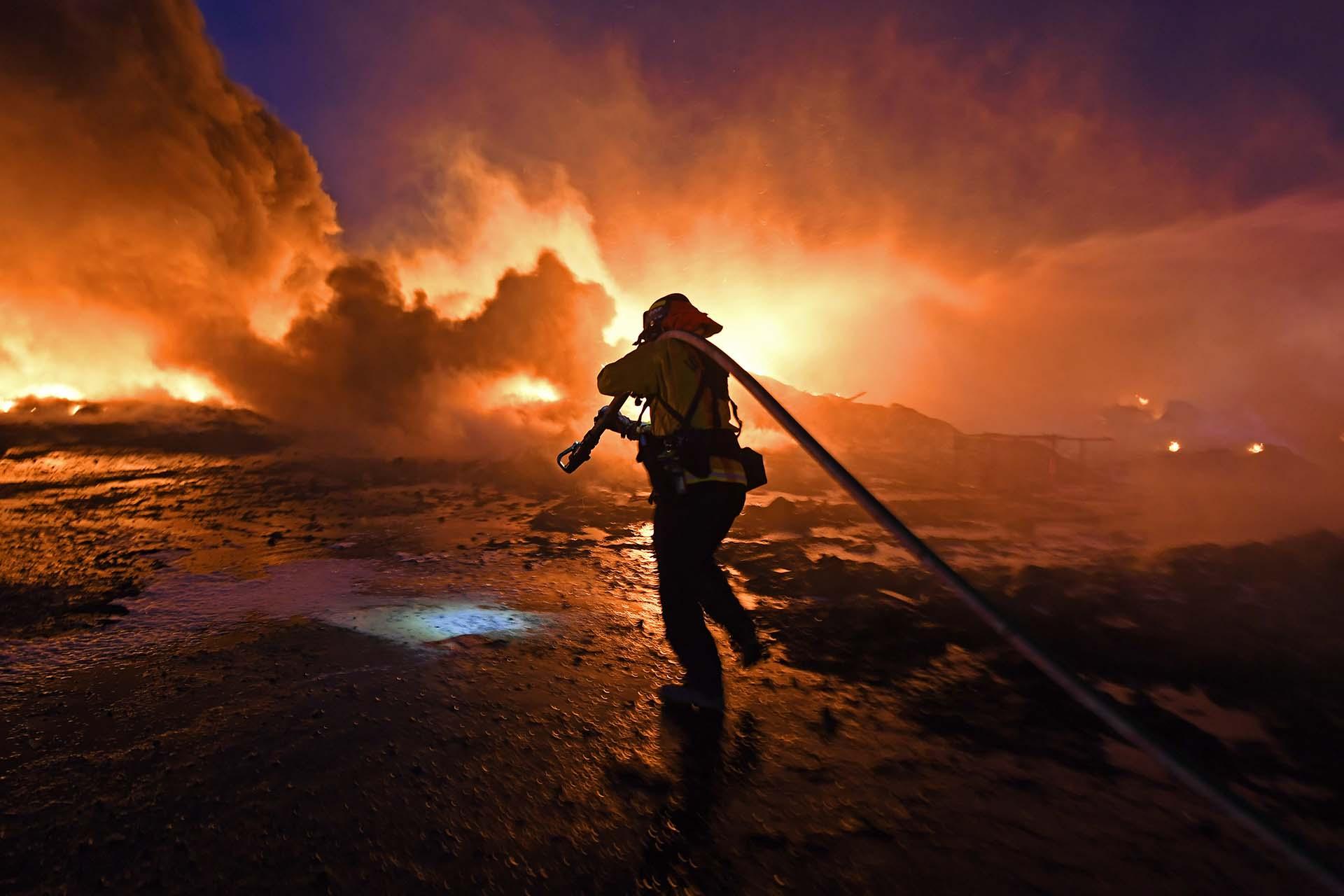 Un bombero arrastra una manguera más cerca para combatir un incendio de hierba en East Cypress Road en Knightsen, California, el domingo por la noche