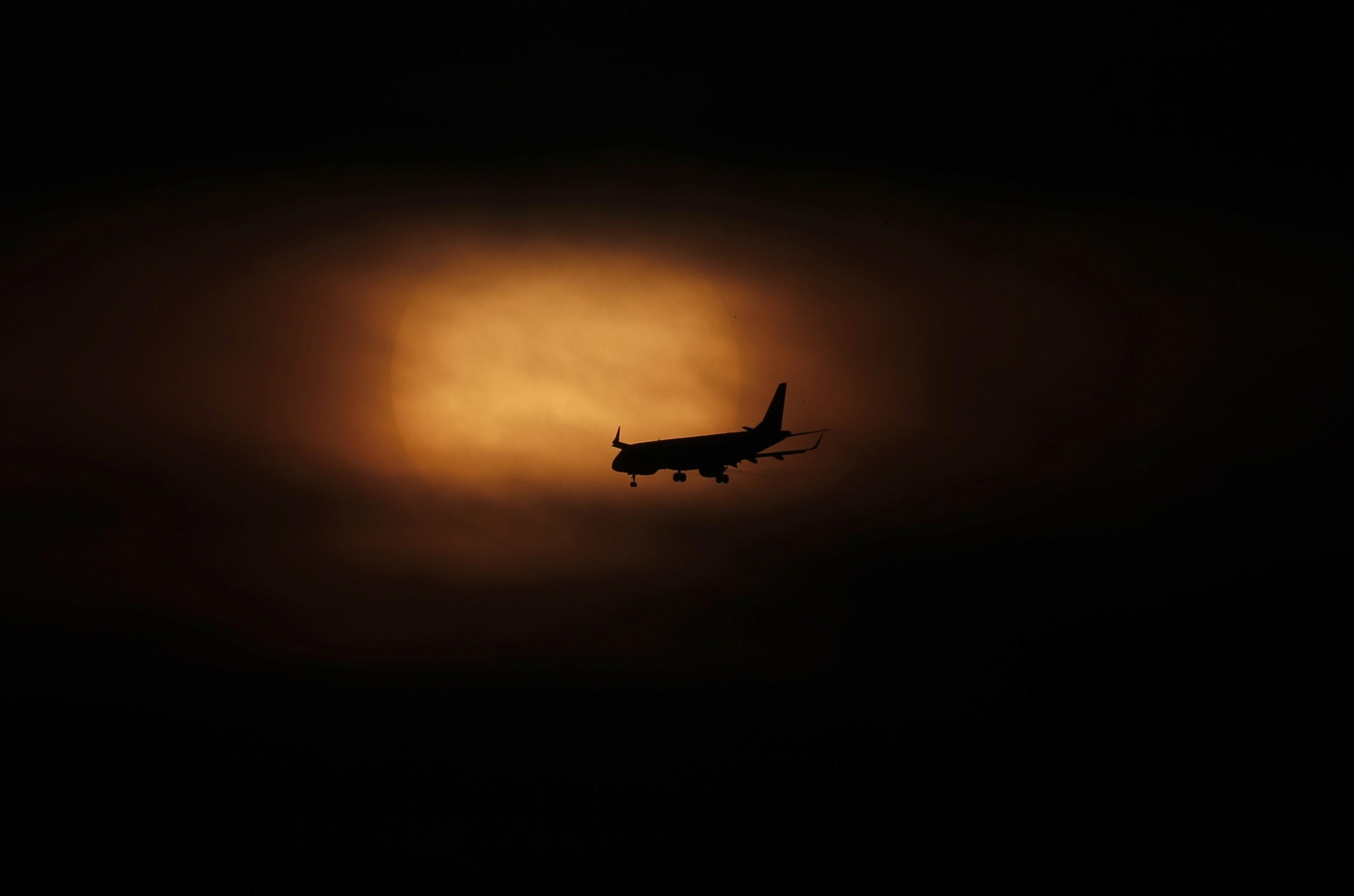 Un avión se prepara para aterrizar cuando sale el sol en la Ciudad de México, el sábado 21 de marzo de 2020.