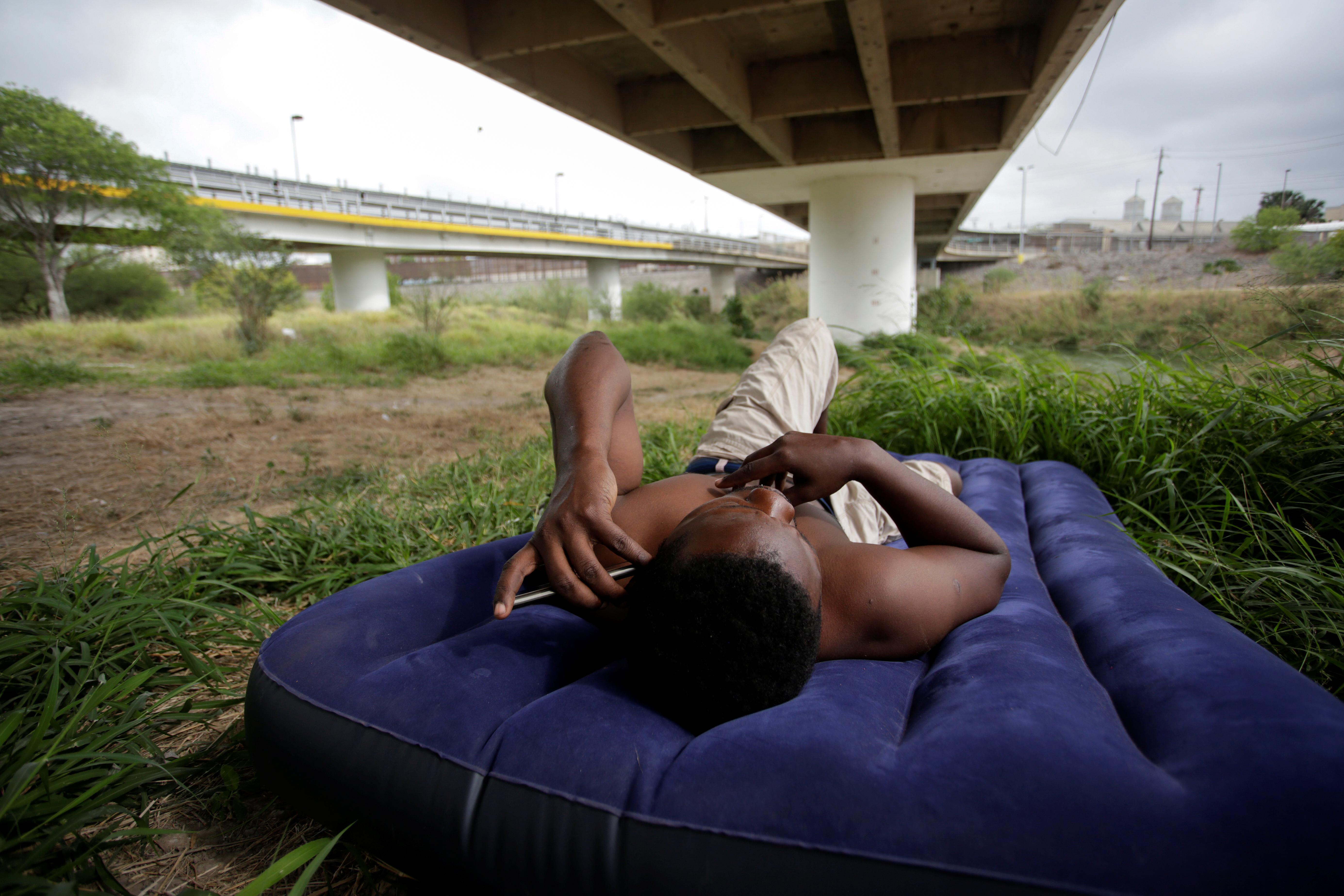 Un migrante de Haití, que busca asilo en los Estados Unidos, descansa bajo el Puente Internacional Matamoros-Brownsville, cerca de un campamento de más de 2,000 migrantes, mientras las autoridades locales se preparan para responder al brote de la enfermedad del coronavirus (COVID-19), en Matamoros , México 20 de marzo de 2020.