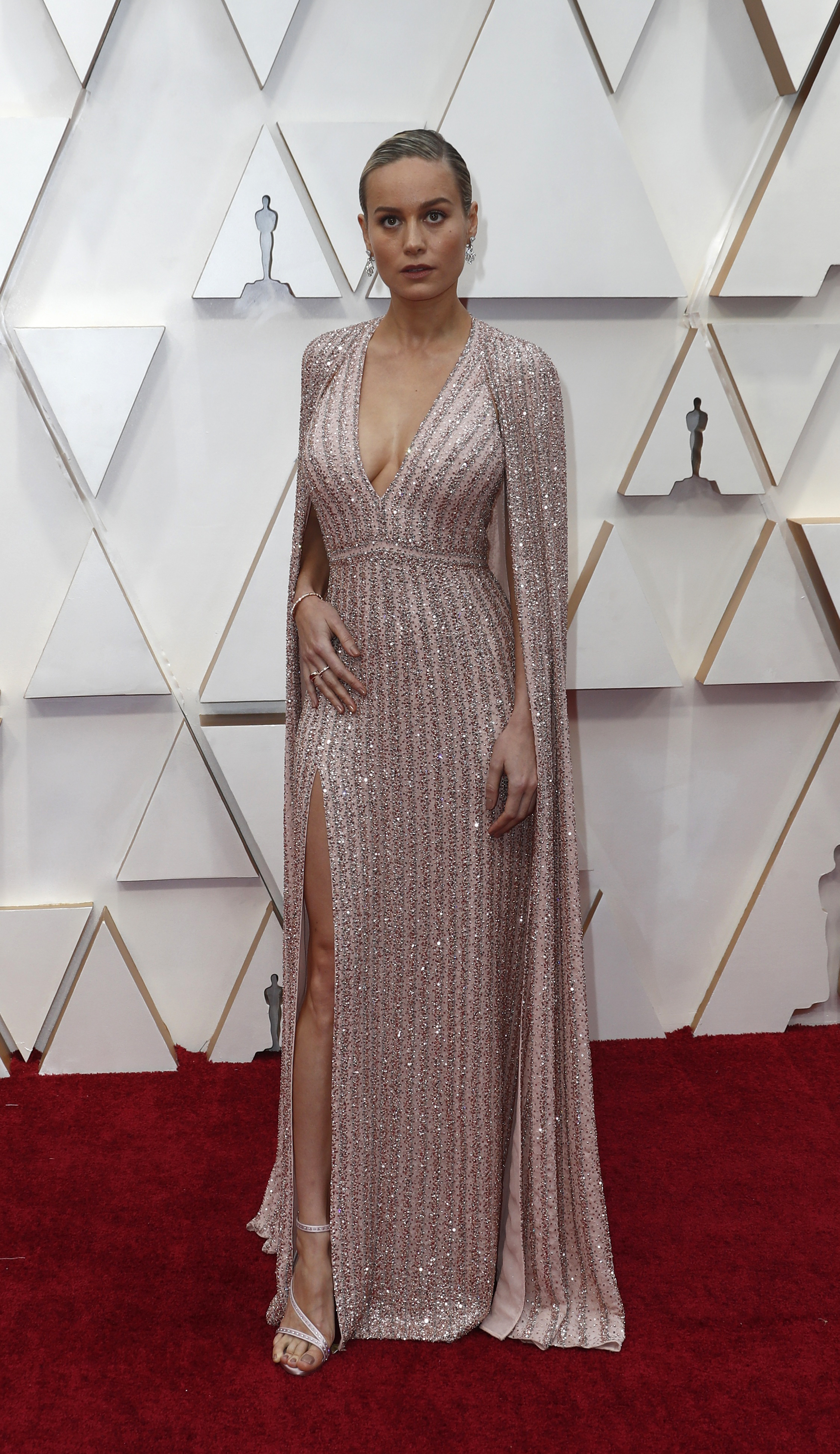 Con un diseño íntegramente bordado con brillantes en color rosa, Brie Larson sorprendió con su pieza joya que tiene un gran escote V, tajo y una capa. Completó el atuendo elegido con sandalias de pulsera y el peinado para los Oscars, un