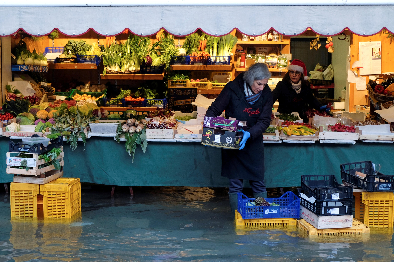 Una mujer lleva una caja delante de su puesto de verduras en Venecia (REUTERS/Manuel Silvestri)
