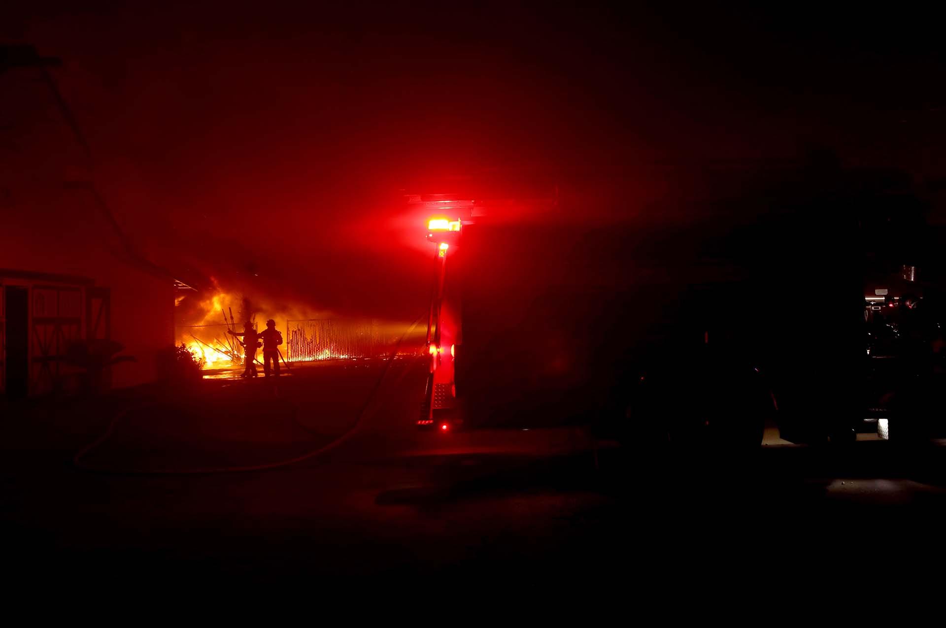 Un bombero sostiene su casco en medio de ráfagas de viento mientras lucha contra el incendio de Kincade en Santa Rosa, California