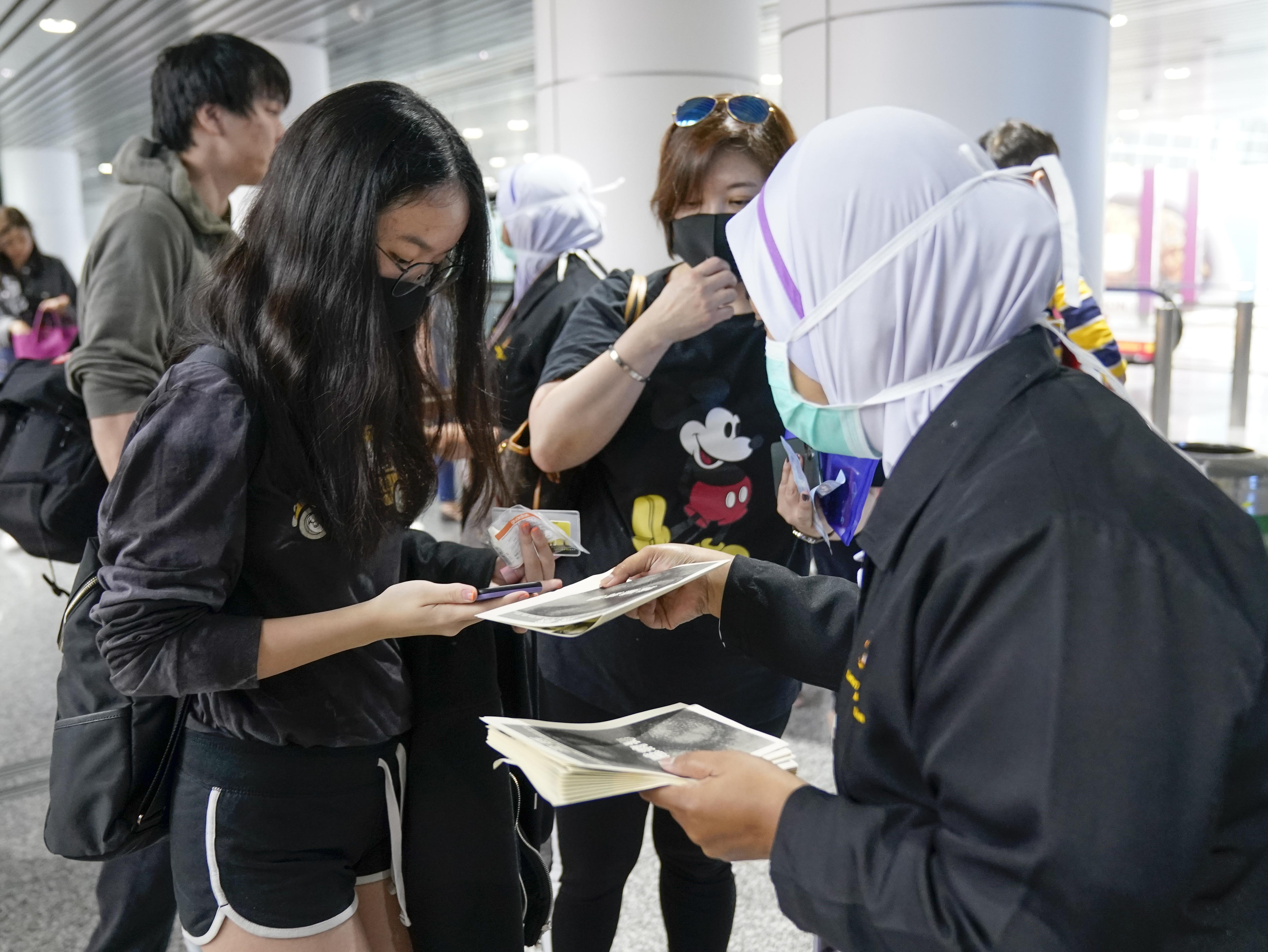 Los funcionarios de salud entregan información sobre el coronavirus actual en el aeropuerto internacional de Kuala Lumpur en Sepang, Malasia, el martes 21 de enero de 2020. Países tanto en Asia-Pacífico como en otros lugares han iniciado controles de temperatura corporal en aeropuertos, estaciones de ferrocarril y a lo largo de carreteras en espera atrapar a quienes corren el riesgo de portar un nuevo coronavirus que ha enfermado a más de 200 personas en China. (Foto AP / Vincent Thian)