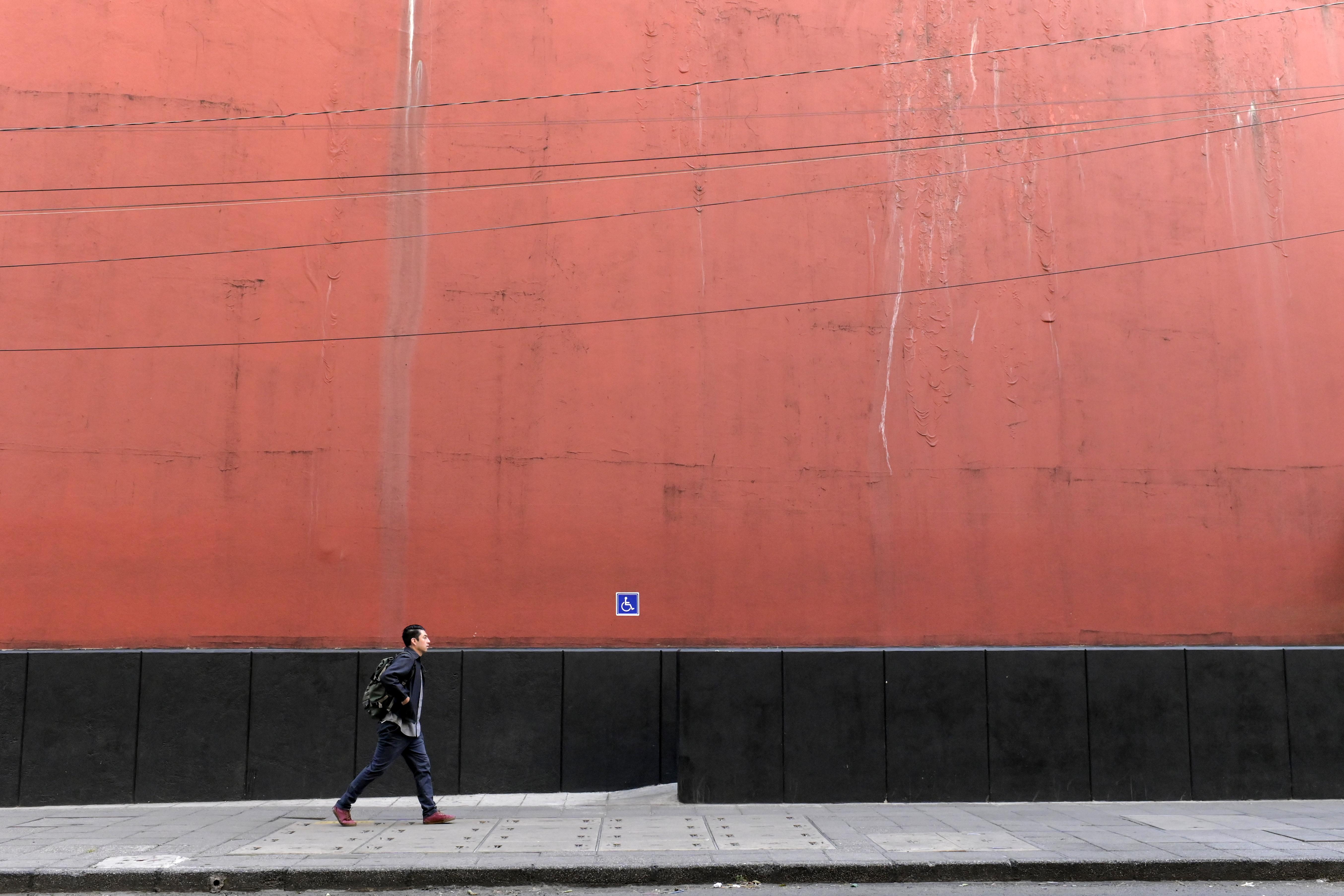 Un hombre camina por una calle en la Ciudad de México el 31 de marzo de 2020, durante el brote del nuevo coronavirus COVID-19.