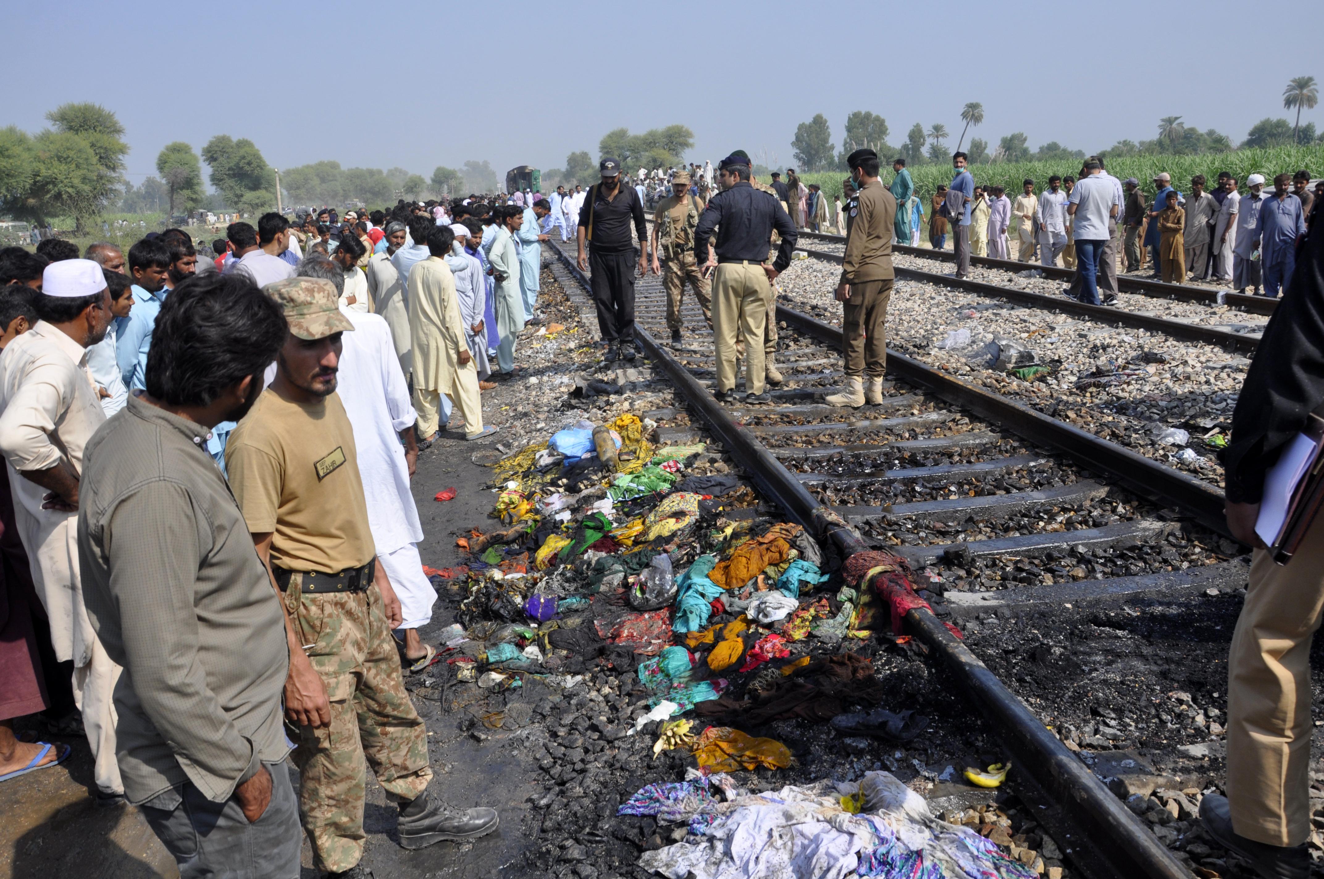 Soldados y funcionarios pakistaníes examinan un tren dañado por un incendio. (Foto AP / Siddique Baluch)