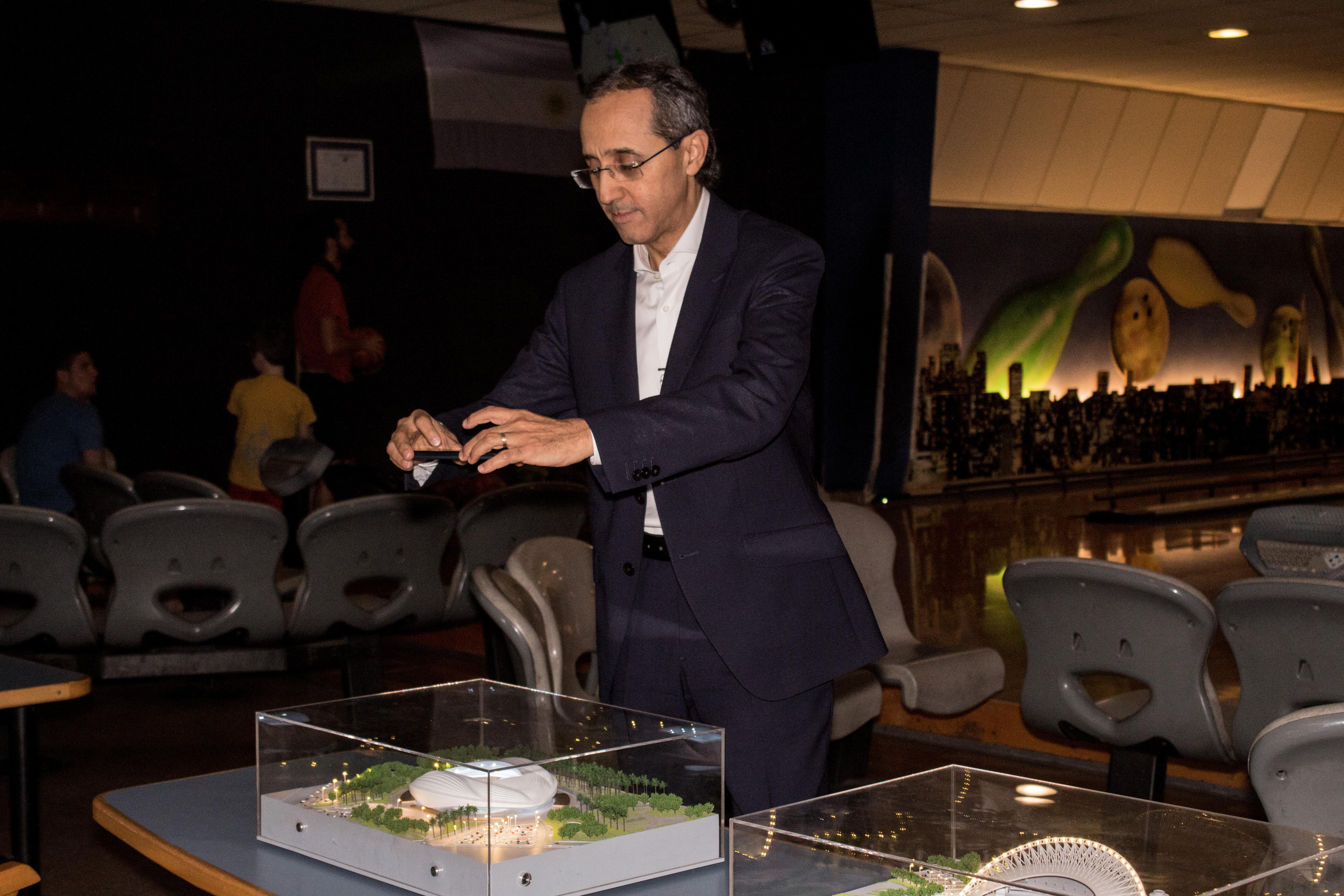 El embajador de Marruecos, Fares Yassir, toma una fotografía de una de las maquetas que se expusieron durante la celebración del Día Nacional del Deporte, con los estadios que actualmente se construyen en Qatar para la Copa del Mundo 2022