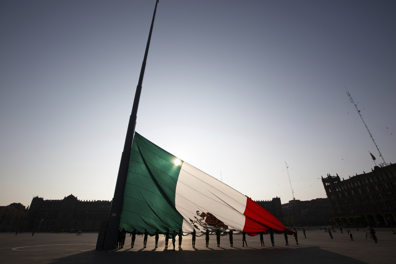 Los soldados mexicanos despliegan la bandera nacional en la plaza Zócalo en la Ciudad de México, el domingo 22 de marzo de 2020.