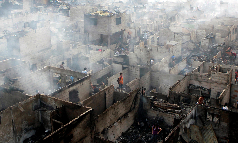 Residentes examinan las ruinas de sus casas después de un incendio en la ciudad de Makati, Metro Manila, Filipinas, el 19 de abril de 2011 (REUTERS/Erik de Castro)