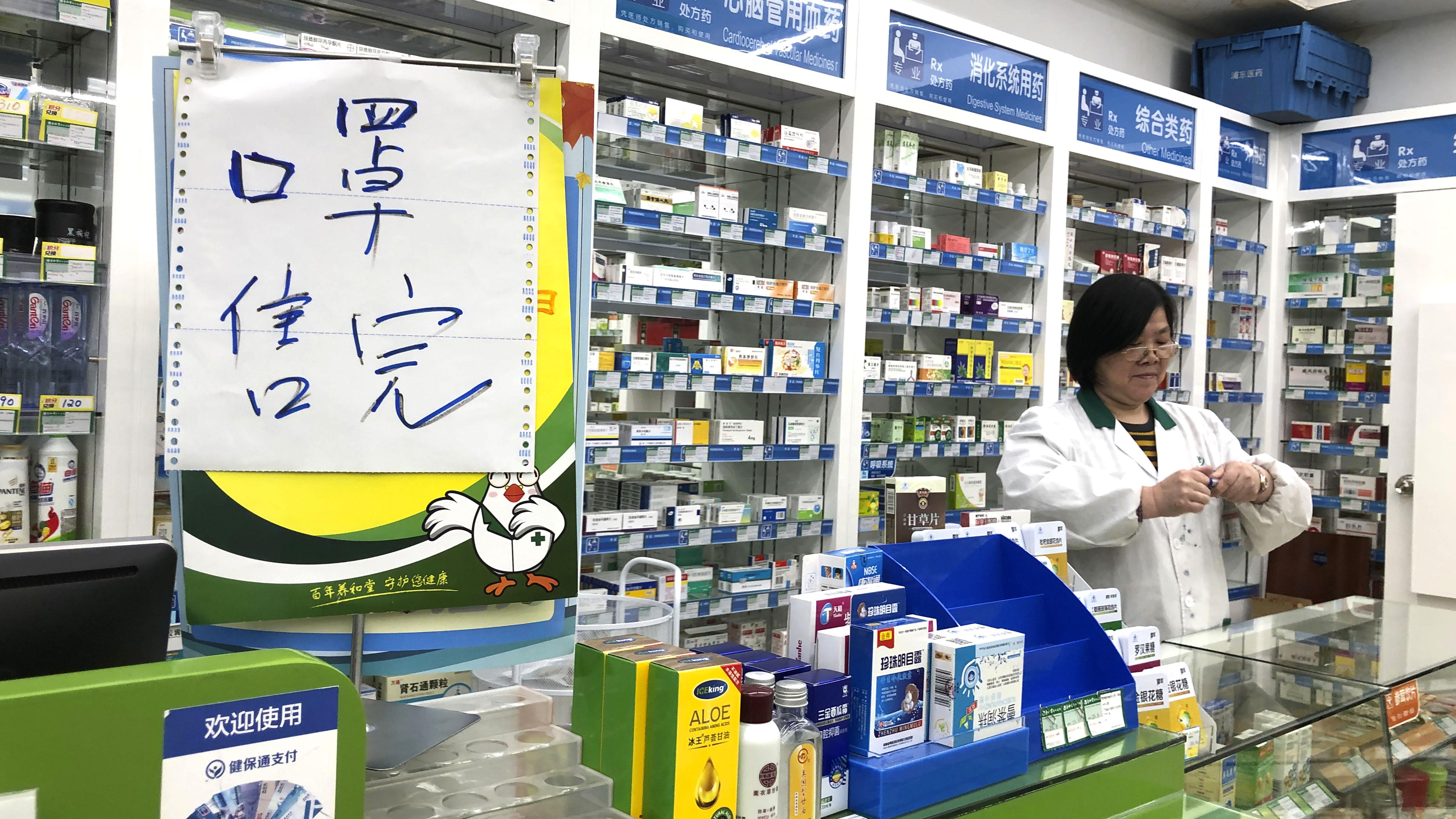 El farmacéutico Liu Zhuzhen se encuentra cerca de un letrero que dice