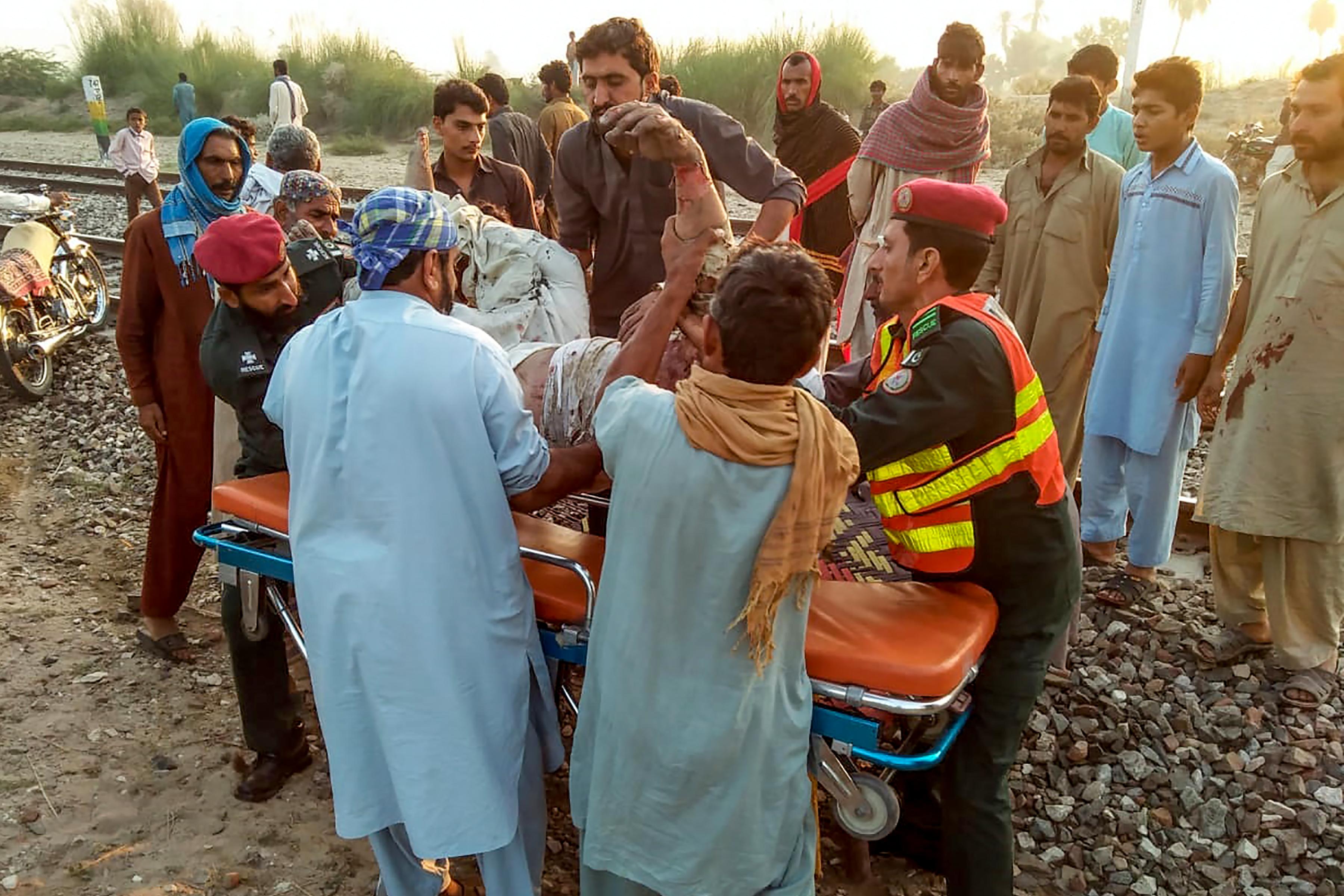 Los equipos de rescate mueven a una víctima herida en el sitio después de que un tren de pasajeros se incendió cerca de Rahim Yar Khan en la provincia de Punjab. (AFP / Servicio de Emergencia de Punjab de Pakistán)