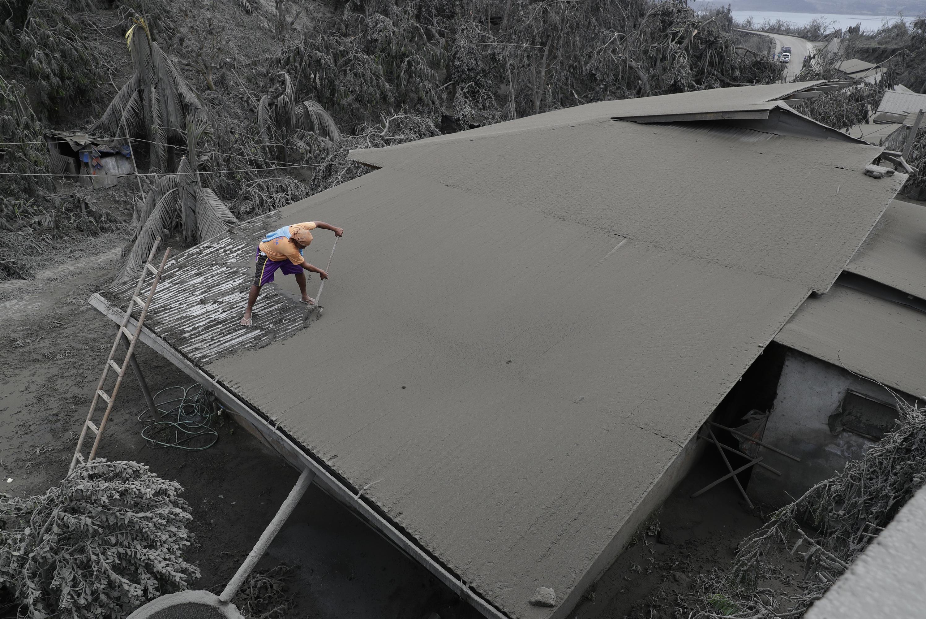 Un residente despeja las cenizas volcánicas de su techo en Laurel, provincia de Batangas, en el sur de Filipinas. (Foto AP / Aaron Favila)