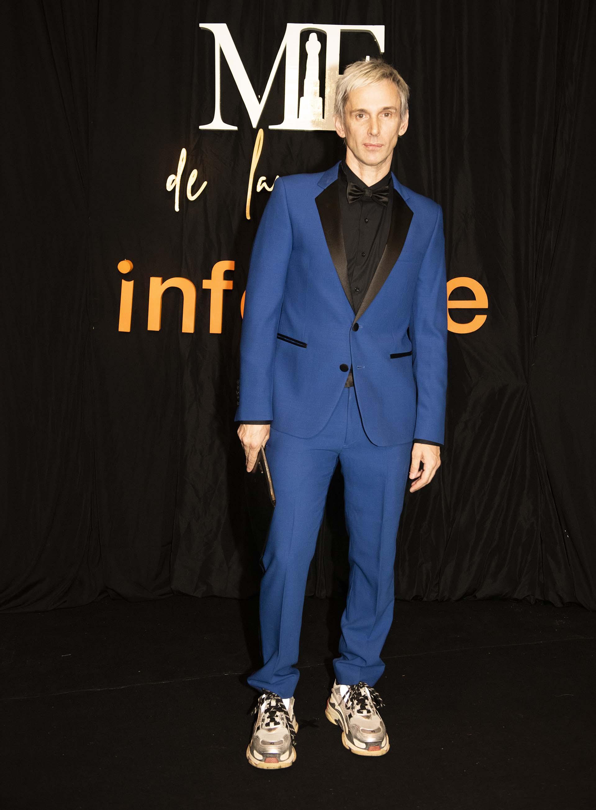 El diseñador Fabián Paz con un look descontracturado de traje azul y negro, combinado con unas