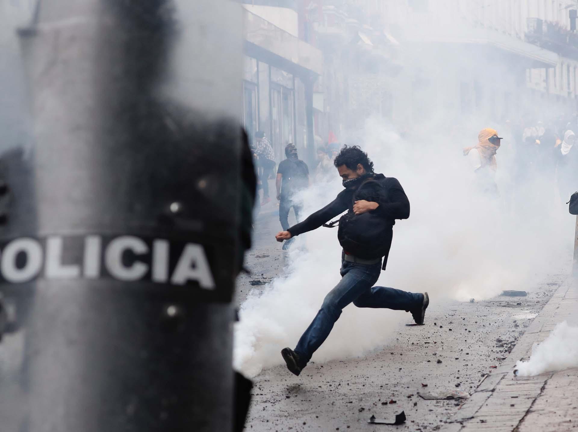 Un joven patea una bomba lacrimógena arrojada por la policía (AP Photo/Dolores Ochoa)