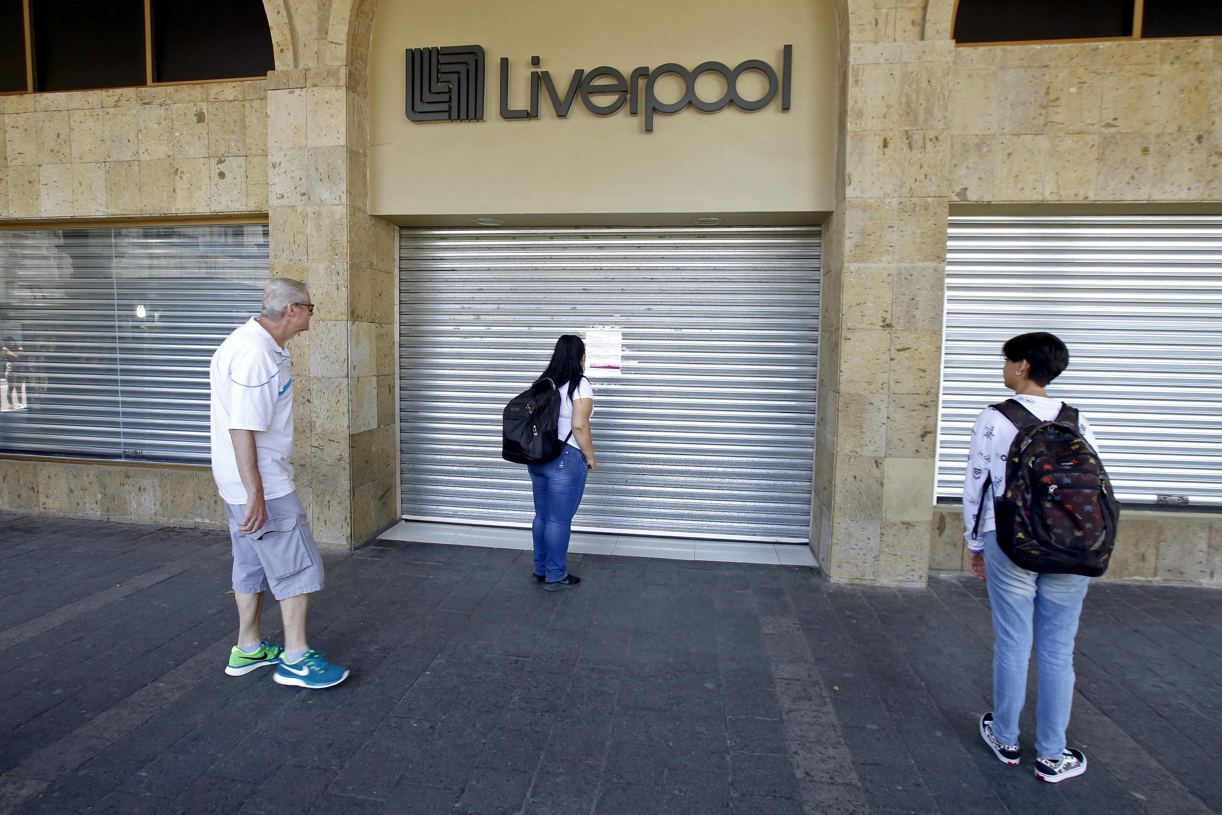 Una mujer mira un aviso dejado en una entrada de los grandes almacenes de Liverpool después de que cerró sus puertas debido a la nueva pandemia de coronavirus COVID-19, en Guadalajara, México, el 31 de marzo de 2020.