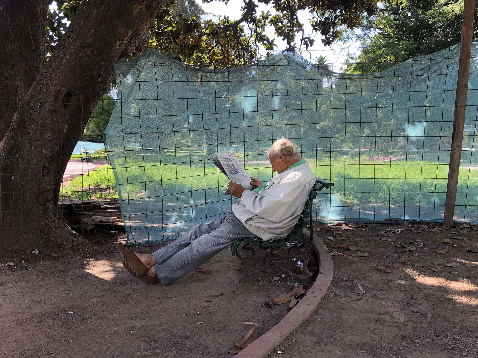 Un hombre leyendo un diario en un domingo de muchísimo calor en febrero de 2019 bajo la sombra de un árbol del Parque Rivadavia. Al artista reflexionó: